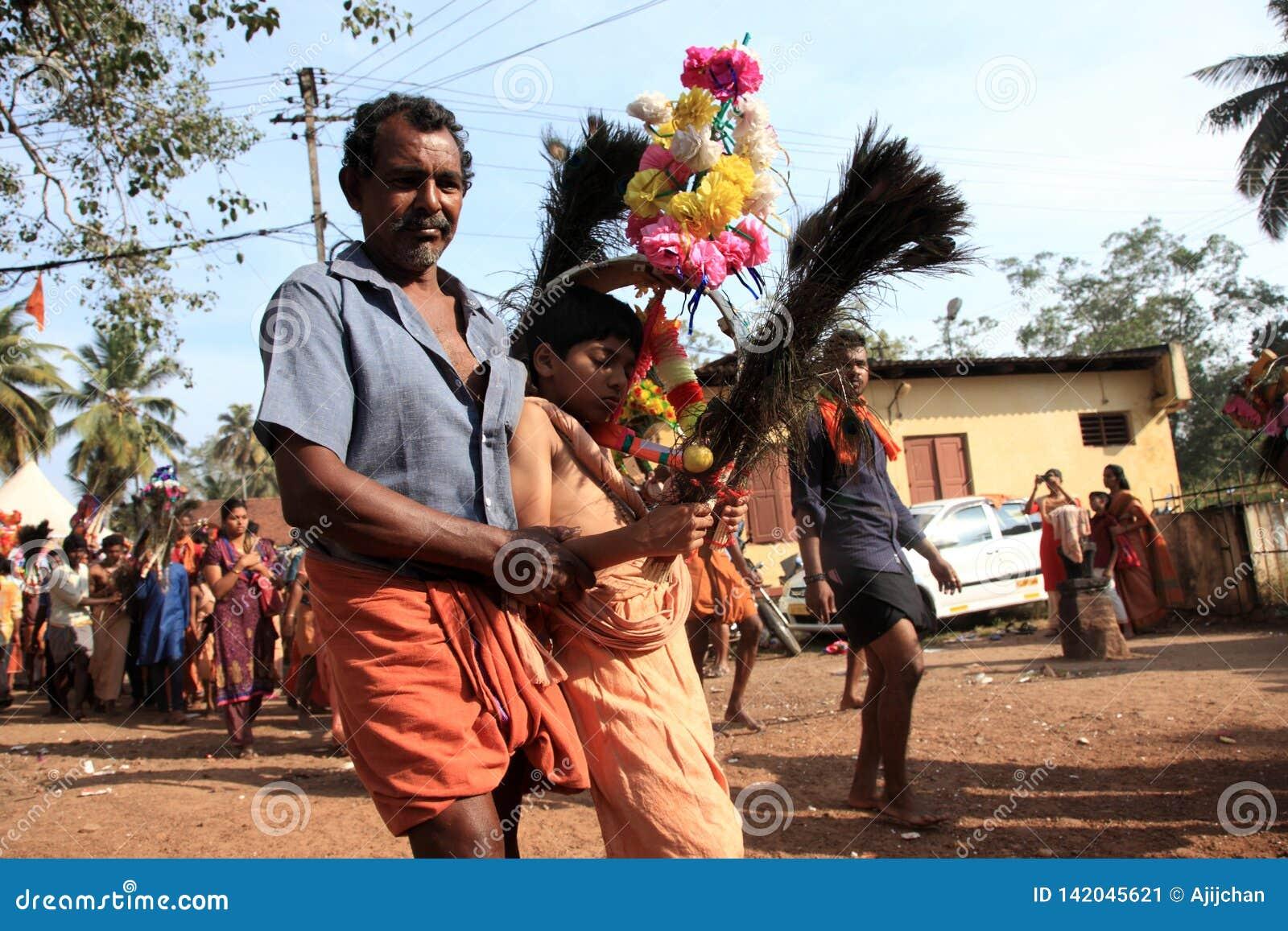 Подвижники держат украшенный свод и танец в остервенении во время фестиваля Thaipuyam