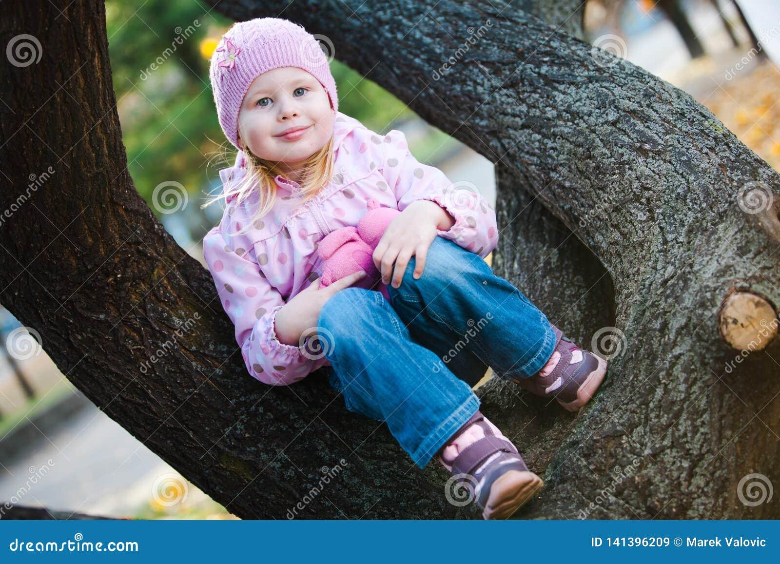 Подросткового возраста девушка сидя с плюшевым мишкой на дереве - пурпурной куртке точек
