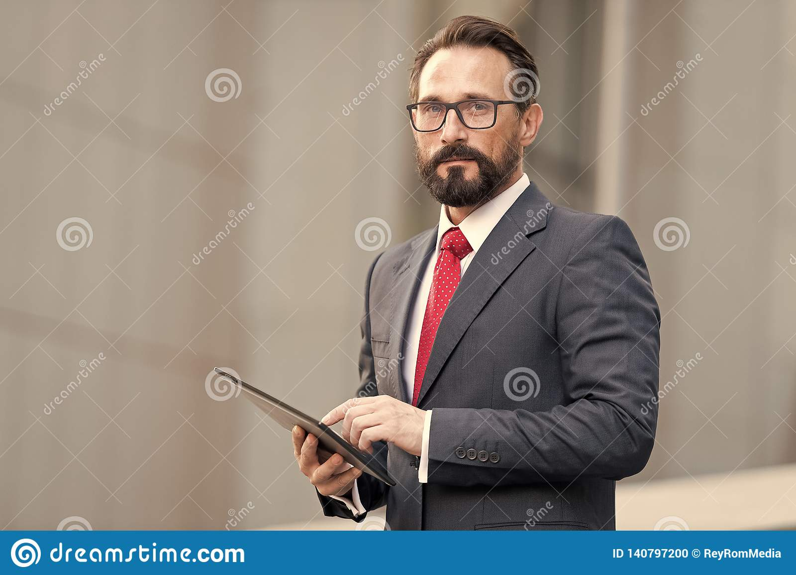 Портрет бизнесмена с таблеткой в руке на предпосылке офисного здания Бизнесмен используя его таблетку из офиса с 4G