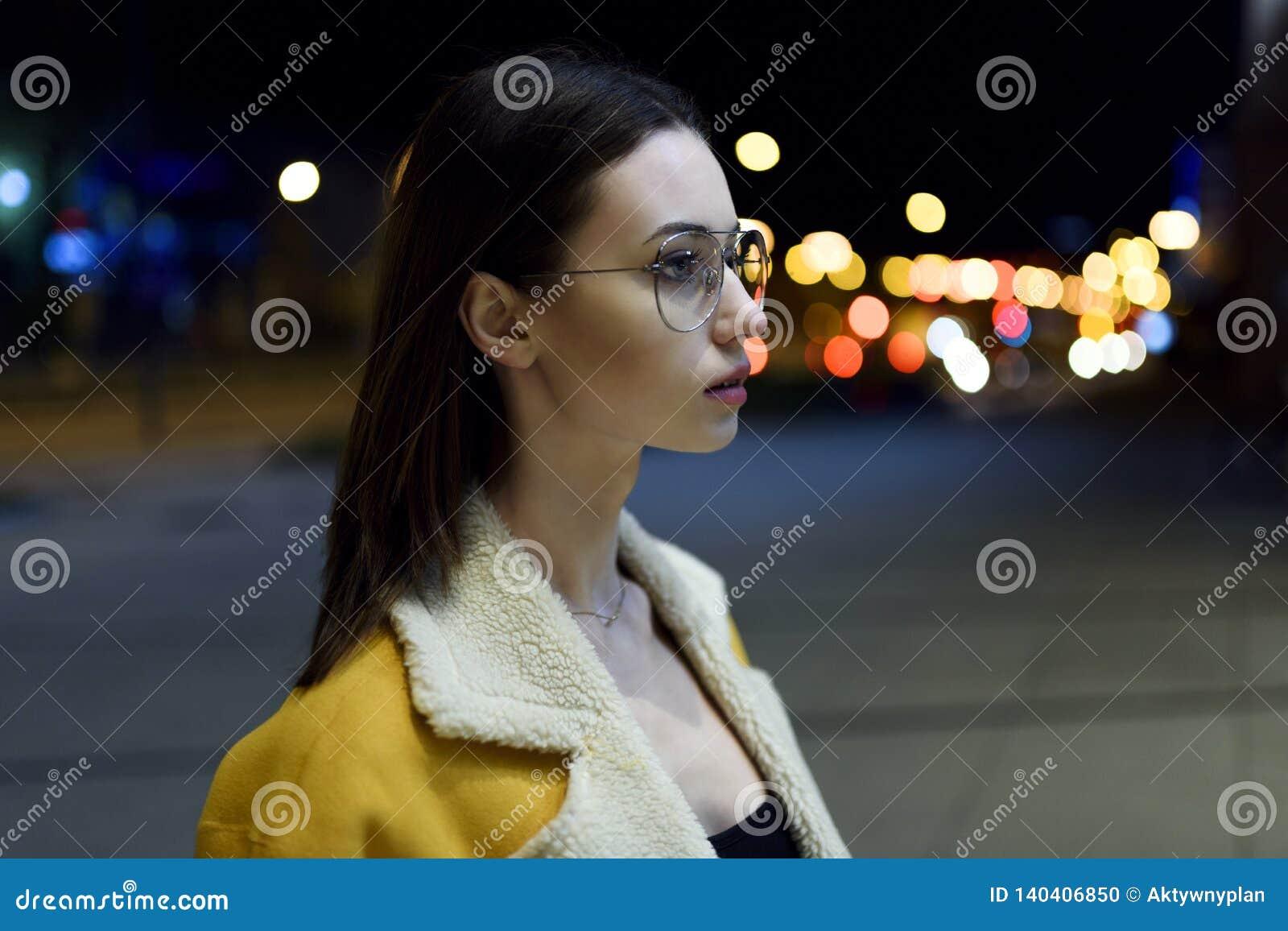 Портрет брюнета в стеклах со стороной повернутой к стороне и освещенной светами центра города Мода Womenswear