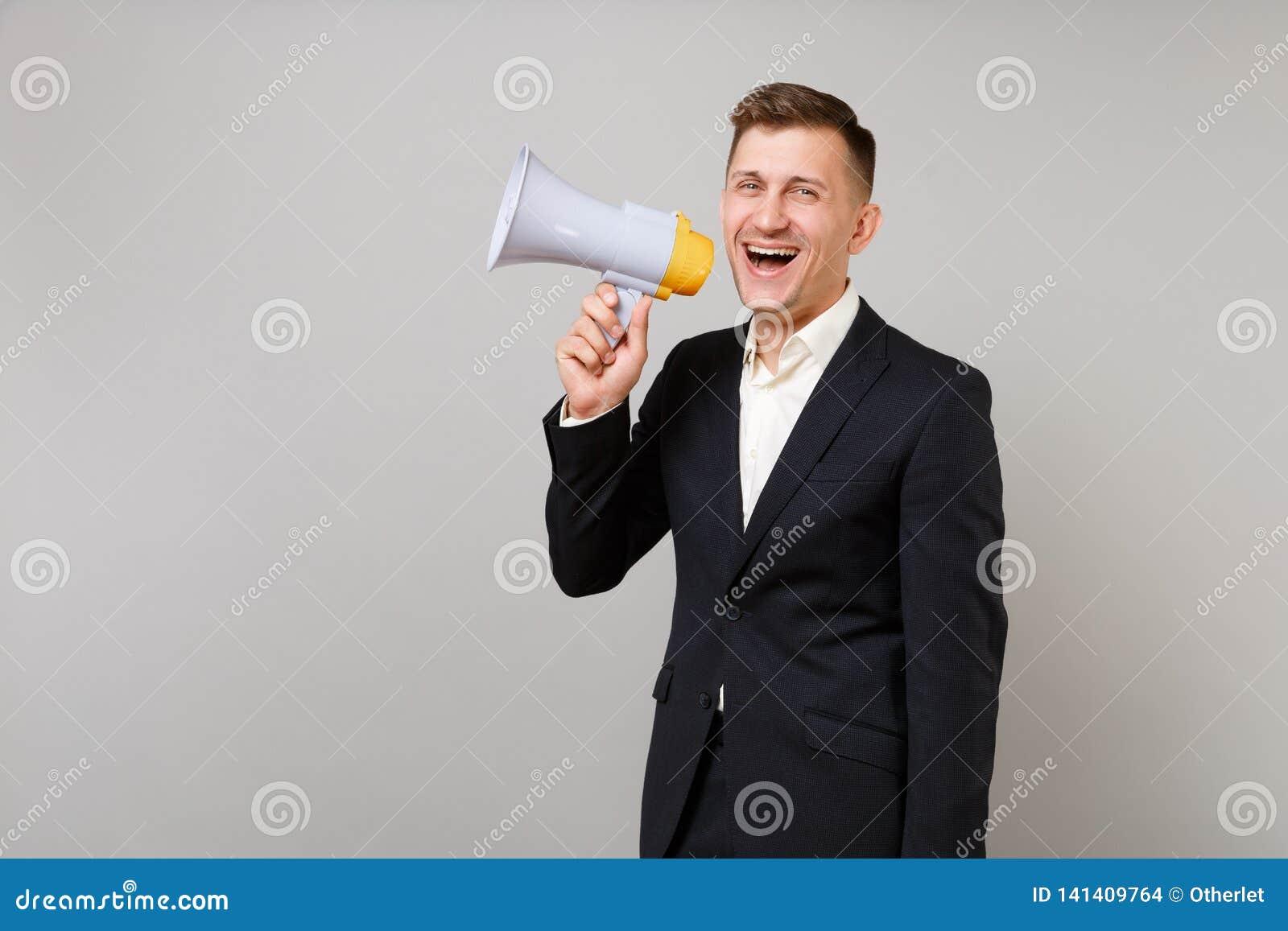 Портрет жизнерадостного молодого бизнесмена в классическом черном костюме, белом мегафоне удерживания рубашки изолированном на се