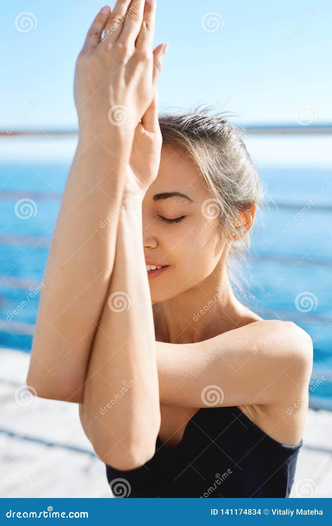 Портрет йоги молодой sporty привлекательной женщины практикуя, делая тренировку оружий Garudasana на пляже с морем