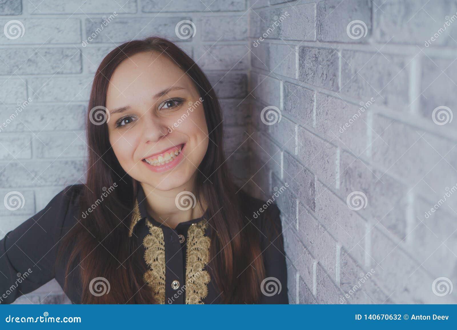 Портрет красивого положения счастья молодой женщины на серой предпосылке кирпича стены grunge текстуры цемента