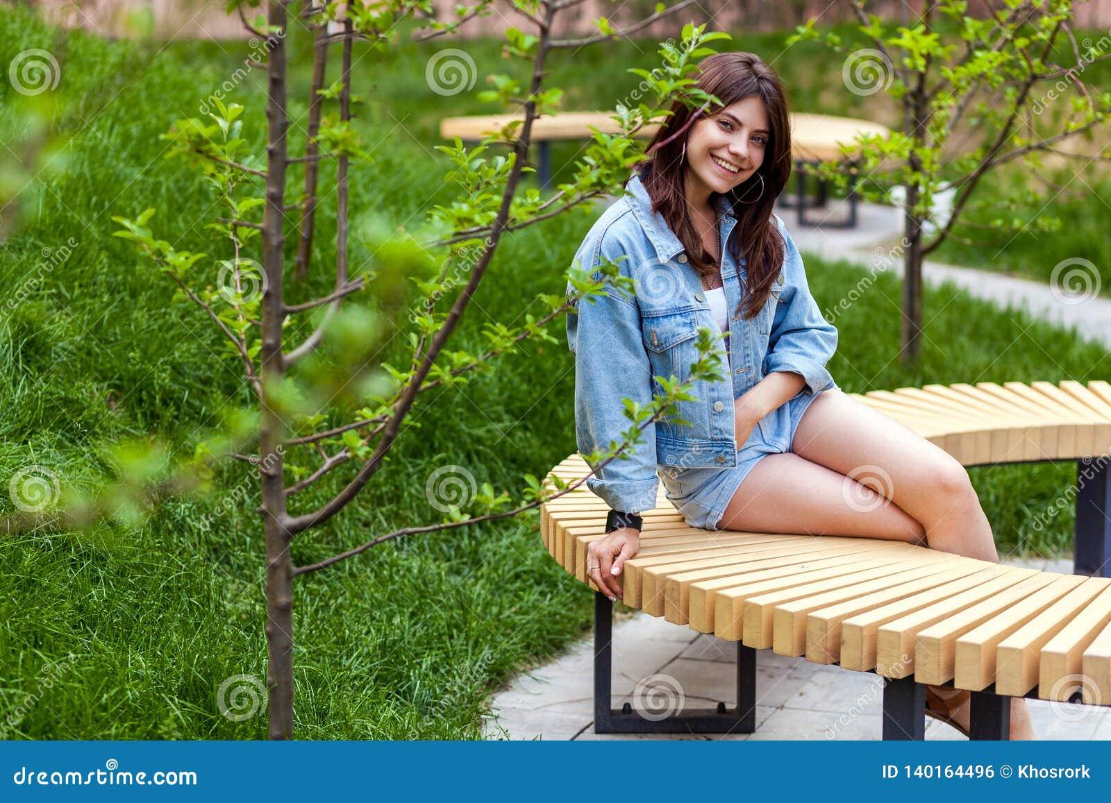 Портрет красивой молодой женщины брюнета в голубом случайном стиле джинсовой ткани сидя и смотря камера с зубастой улыбкой