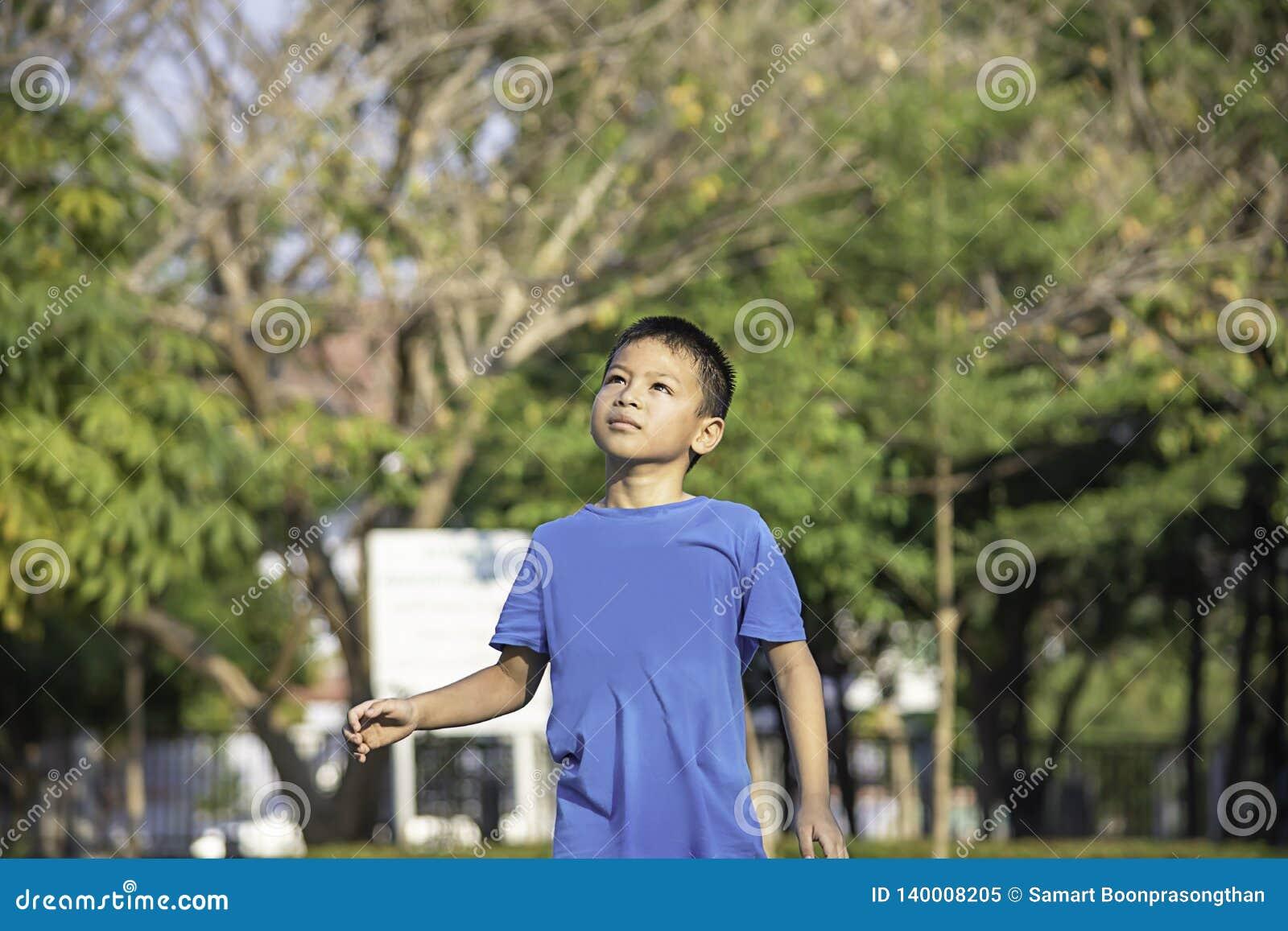 Портрет мальчика Азии смеясь и усмехаясь счастливо деревья предпосылки расплывчатые в парке