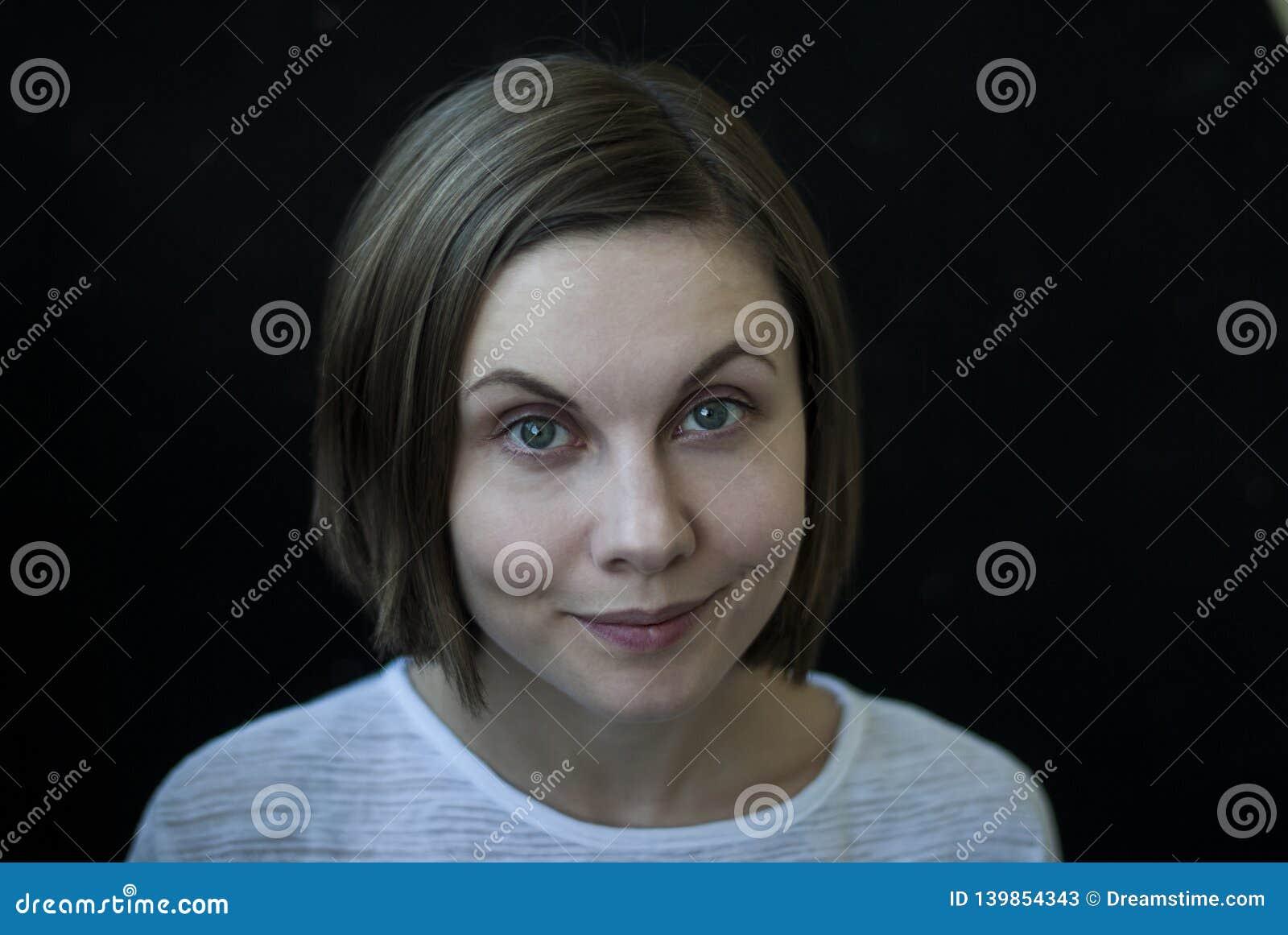 Портрет молодой женщины на черной предпосылке, конце-вверх, выражении лица в реальном маштабе времени