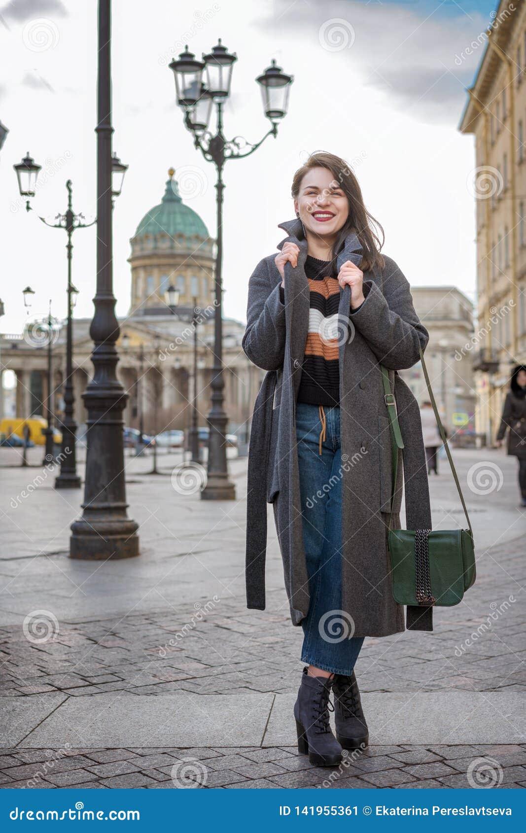 Портрет моды красивой уверенной женщины идя в улицу