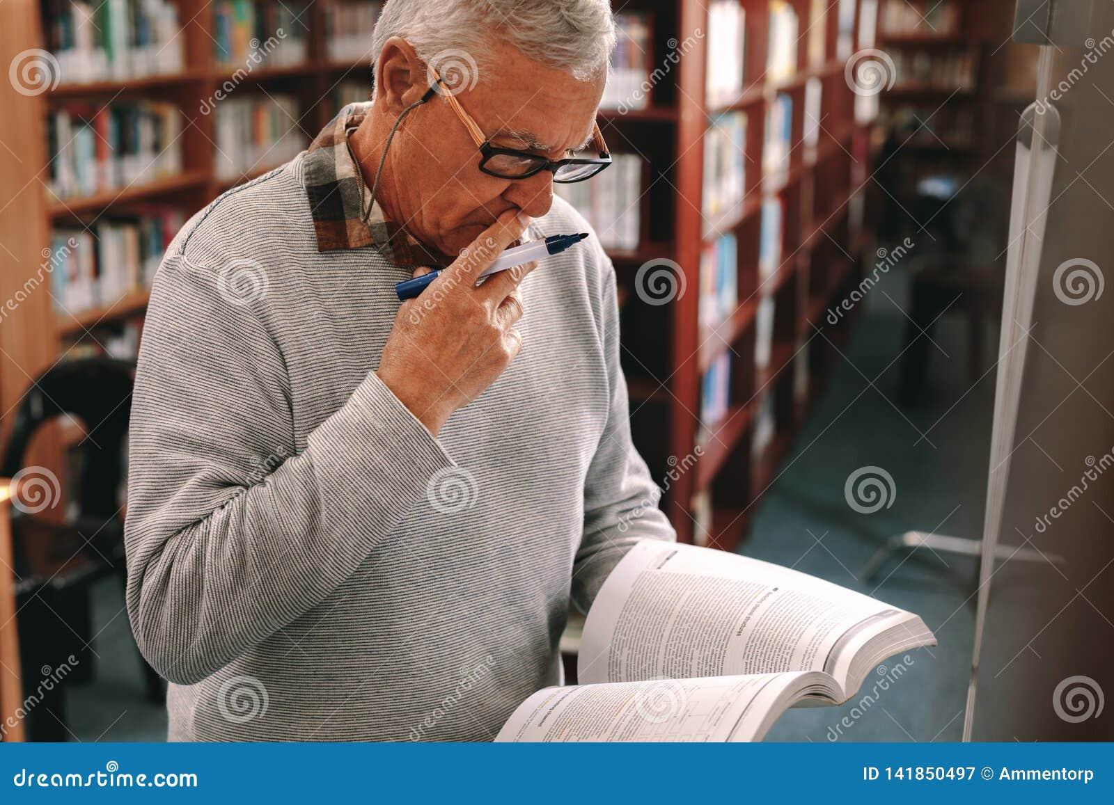 Портрет положения старшего человека в классе держа учебник