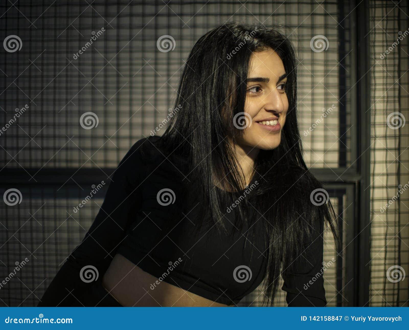 Портрет девушки брюнета в черной верхней части смотря в зеркале в спортзале на фоне решетки