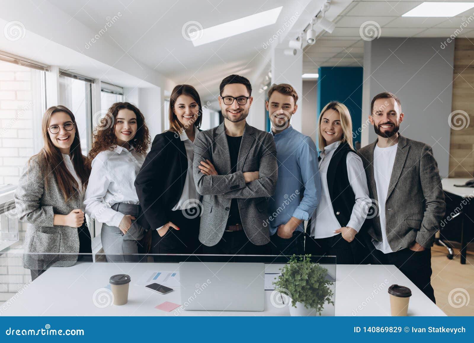 Портрет усмехаясь группы в составе разнообразные корпоративные коллеги стоя в ряд совместно в ярком современном офисе
