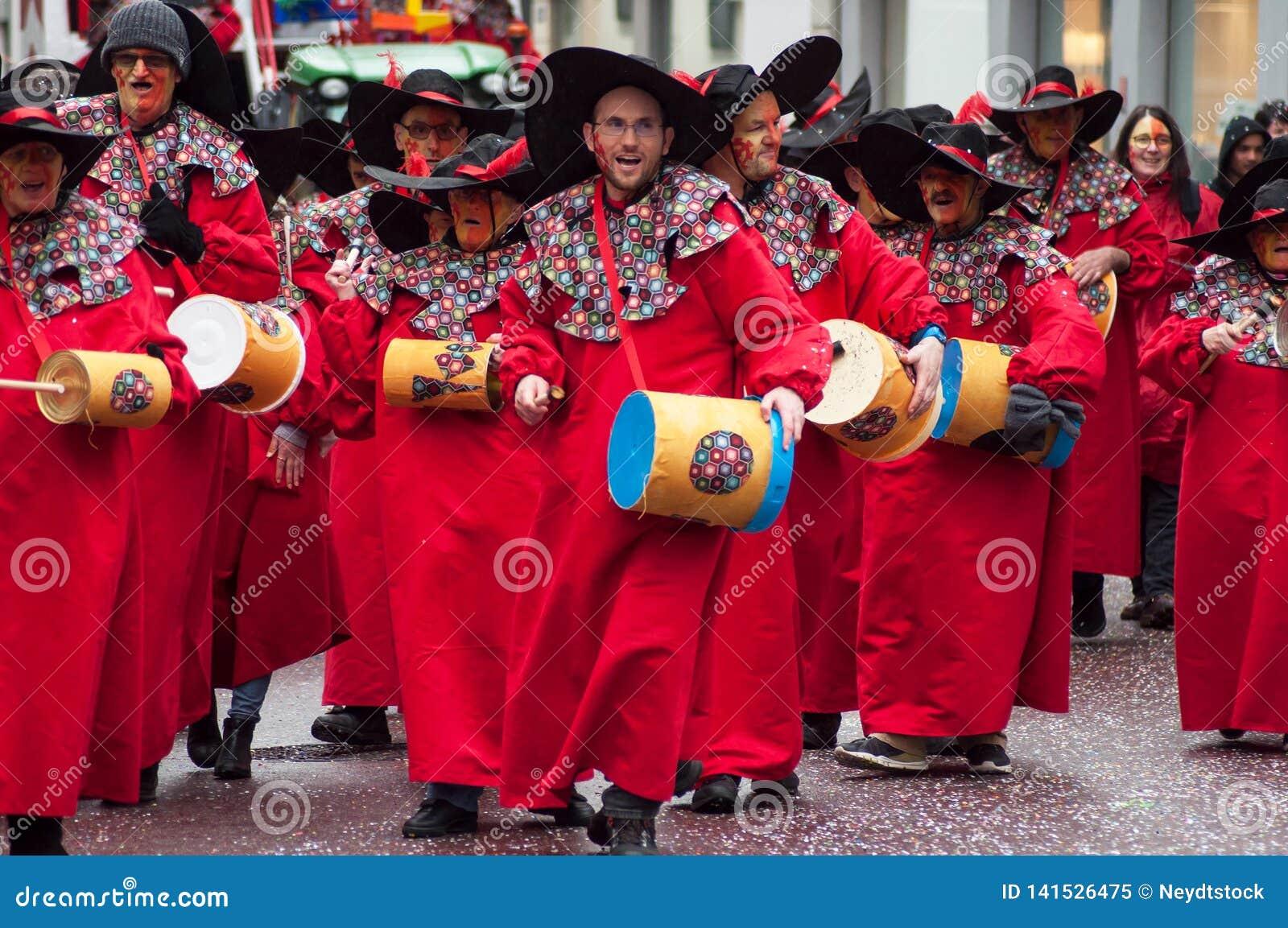 Портрет усмехаясь музыканта с красным костюмом играя барабанчики в улице