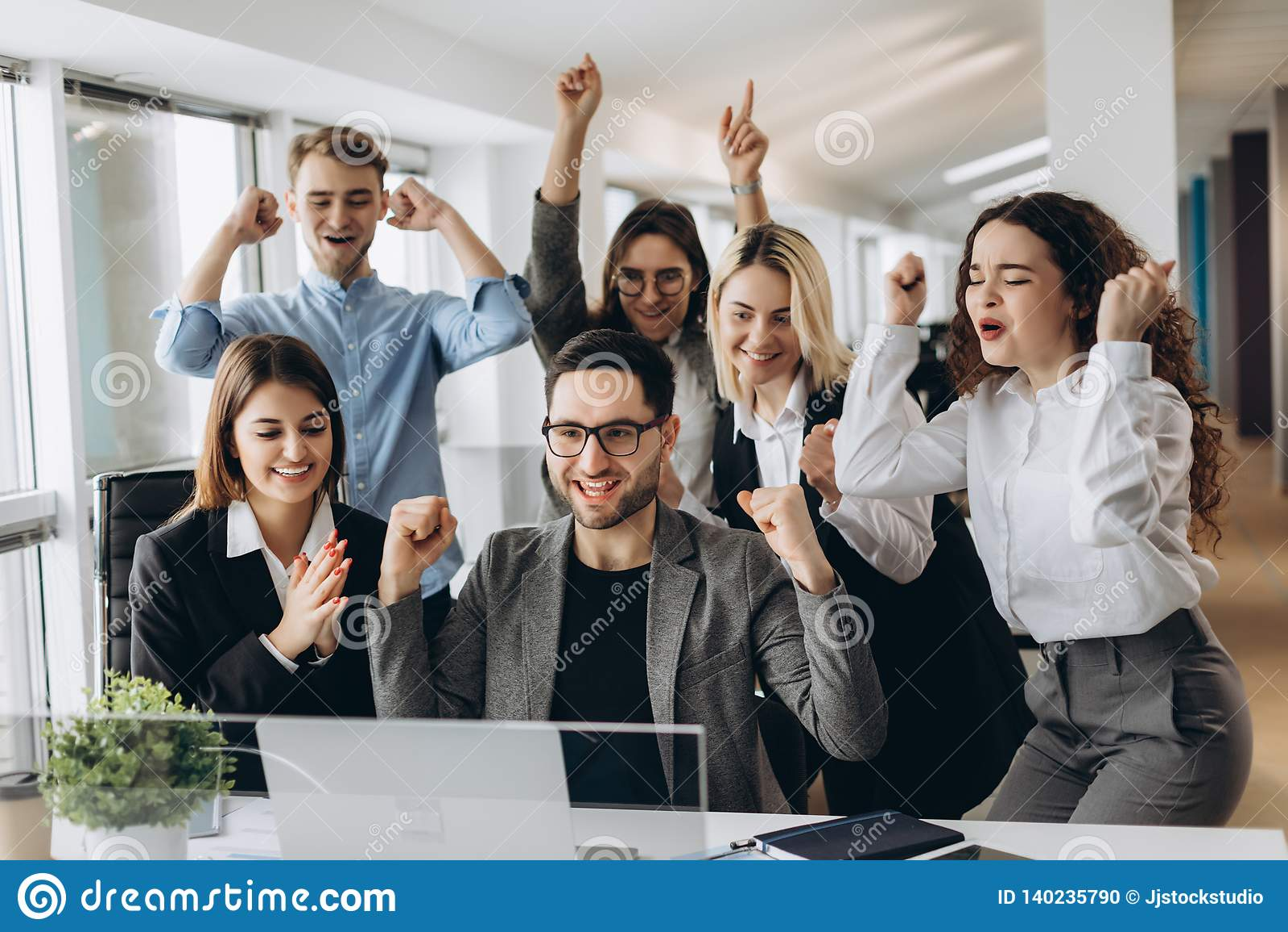 Портрет очень счастливой успешной выразительной показывая жестами команды дела на офисе