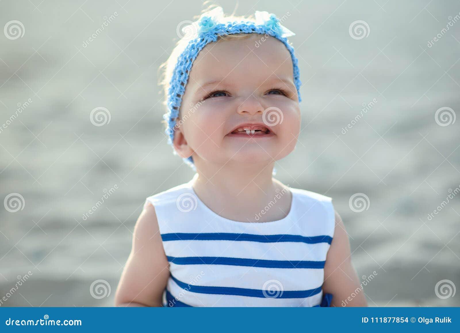 Ð-¡ ute behandla som ett barn flickan i trevlig randig klänning och blåtthuvudbindel som ler och visar hennes mjölktänder