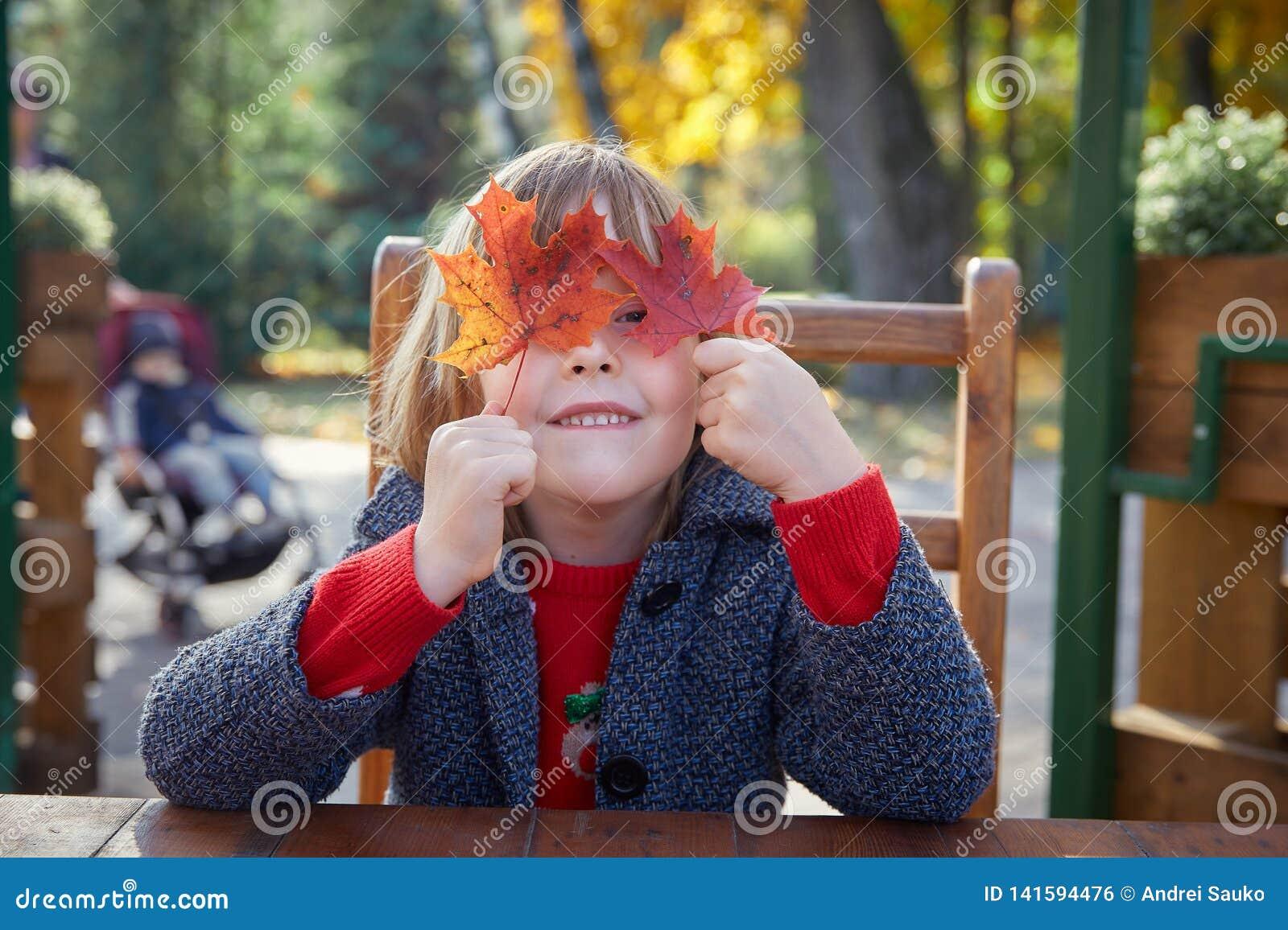Девушка играя с листьями осени