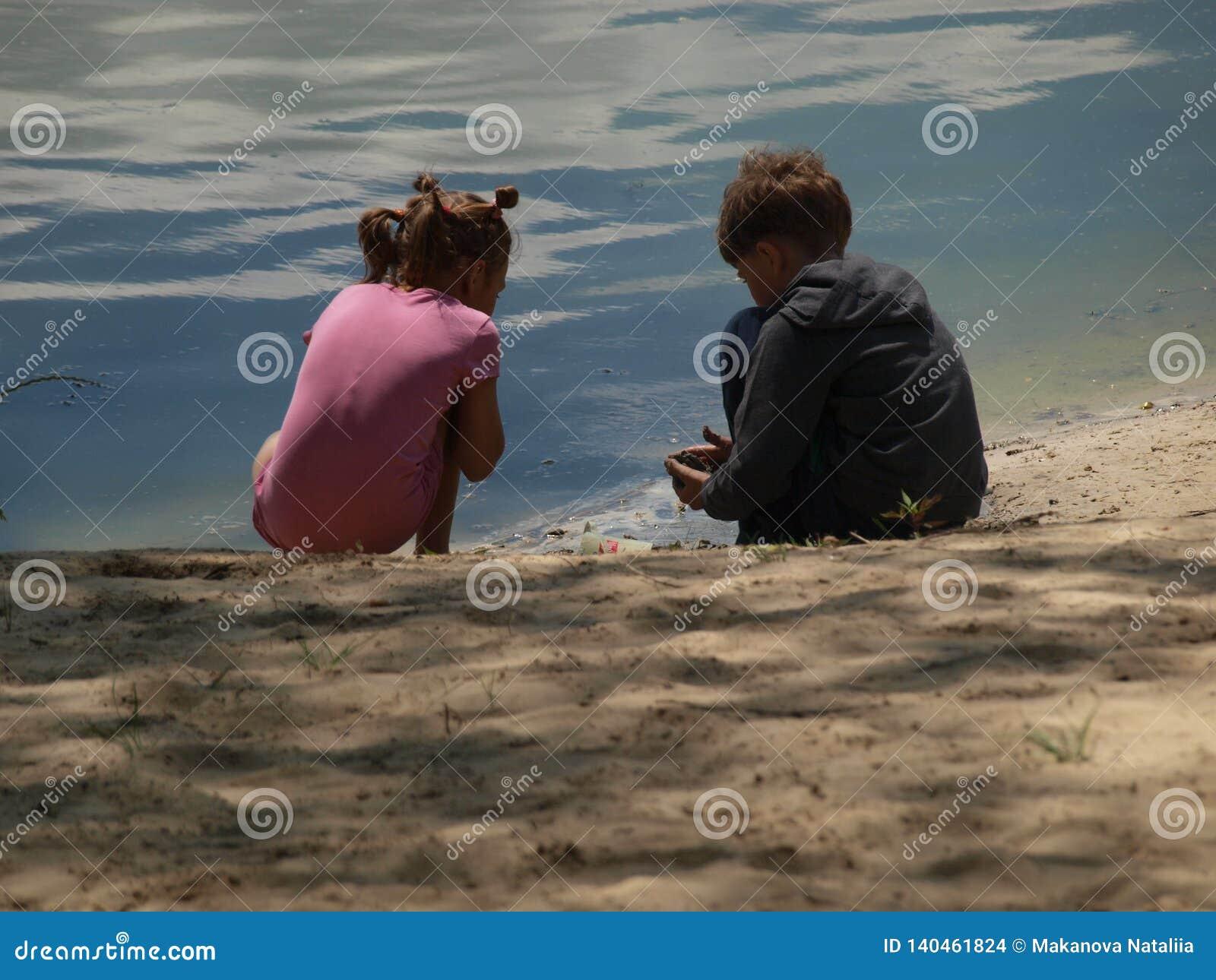 Девушка и мальчик на речном береге играя с песком и водой