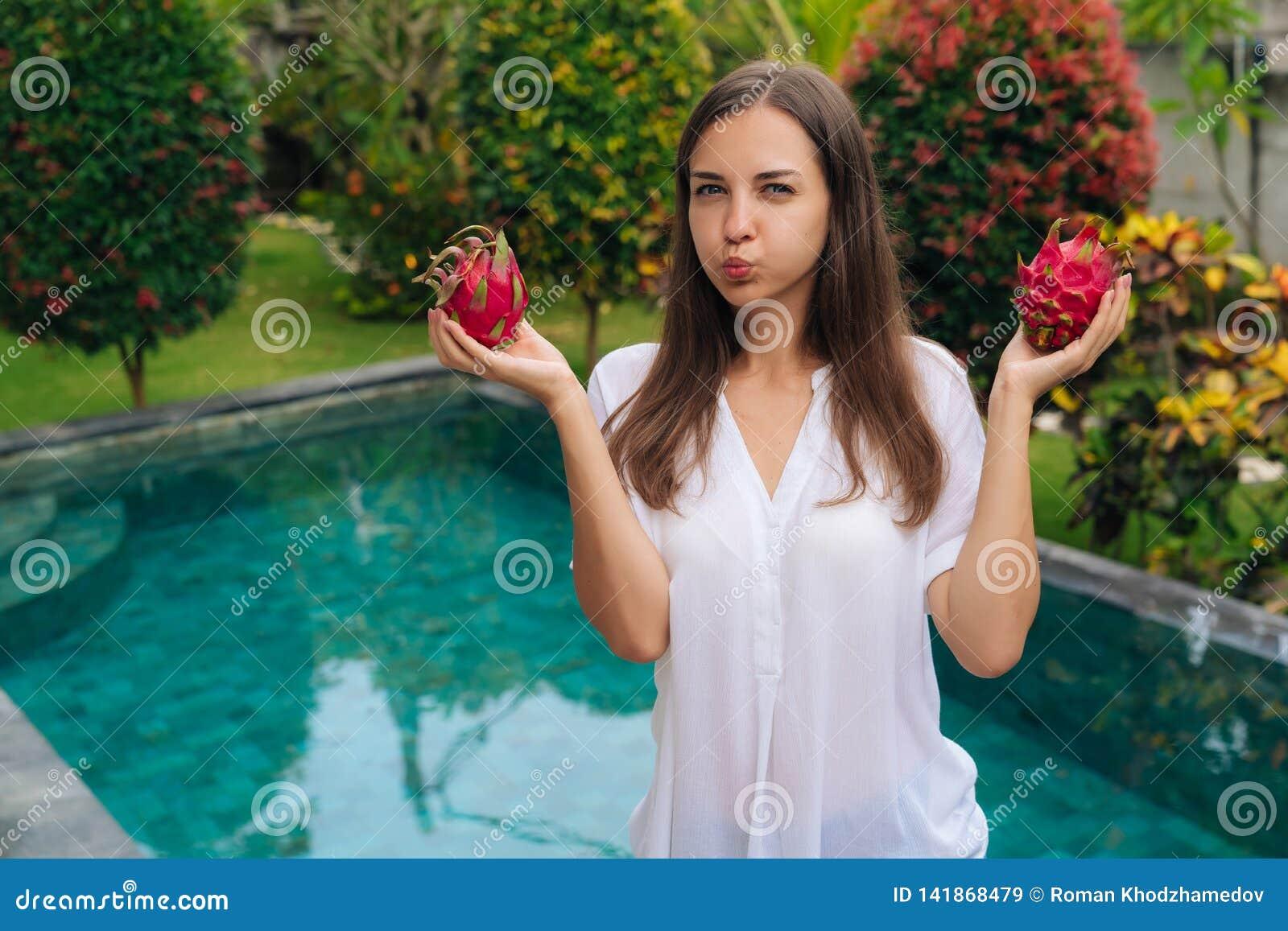 Девушка портрета держит 2 плода дракона, pitaya в ее руках и делает смешную сторону надувает ее щеки