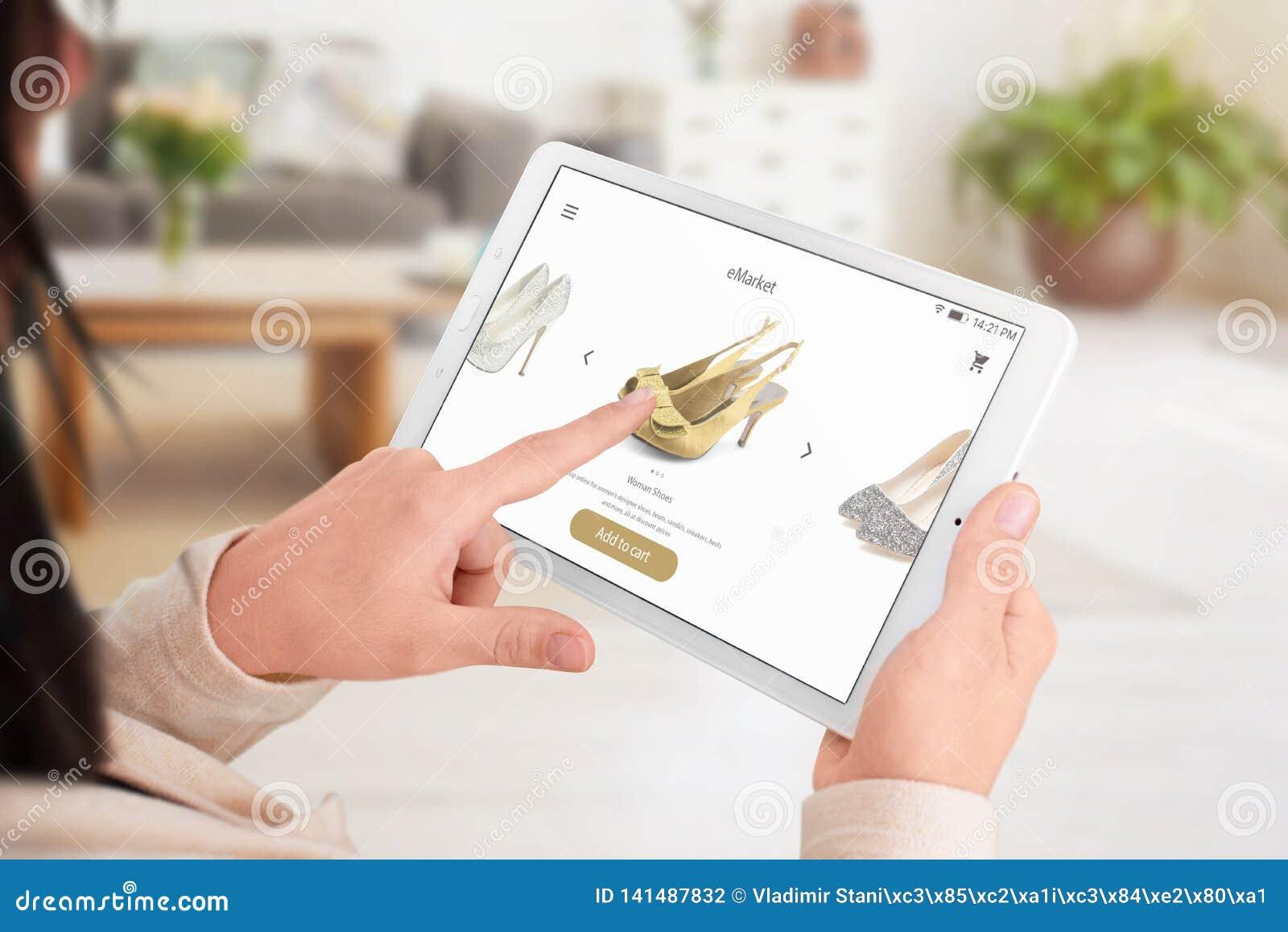 Девушка добавляет ботинки к корзине с онлайн приложением