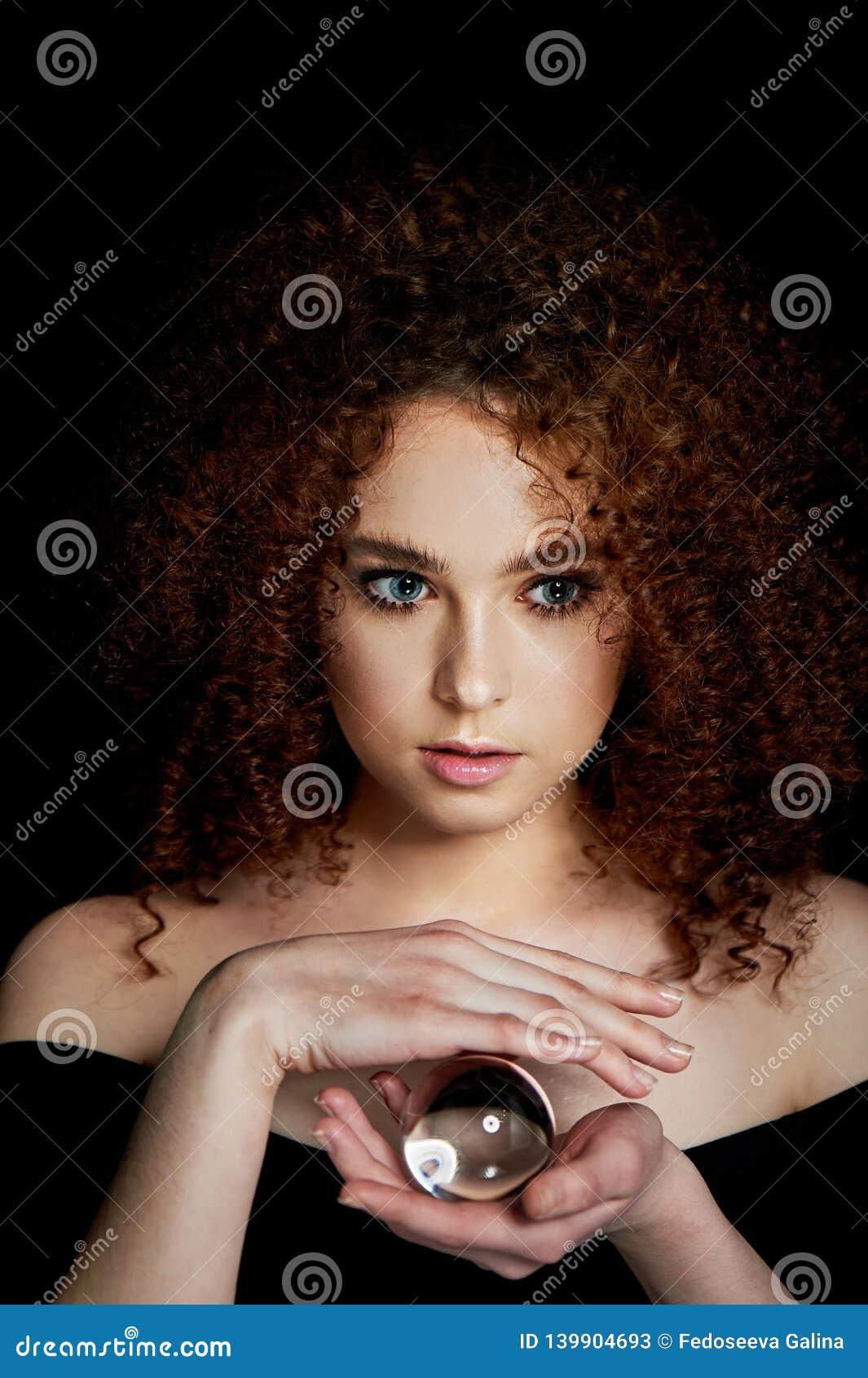 Девушка с сочными курчавыми красными волосами Владения в его руках стеклянный глобус Тайна, предчувствие будущего