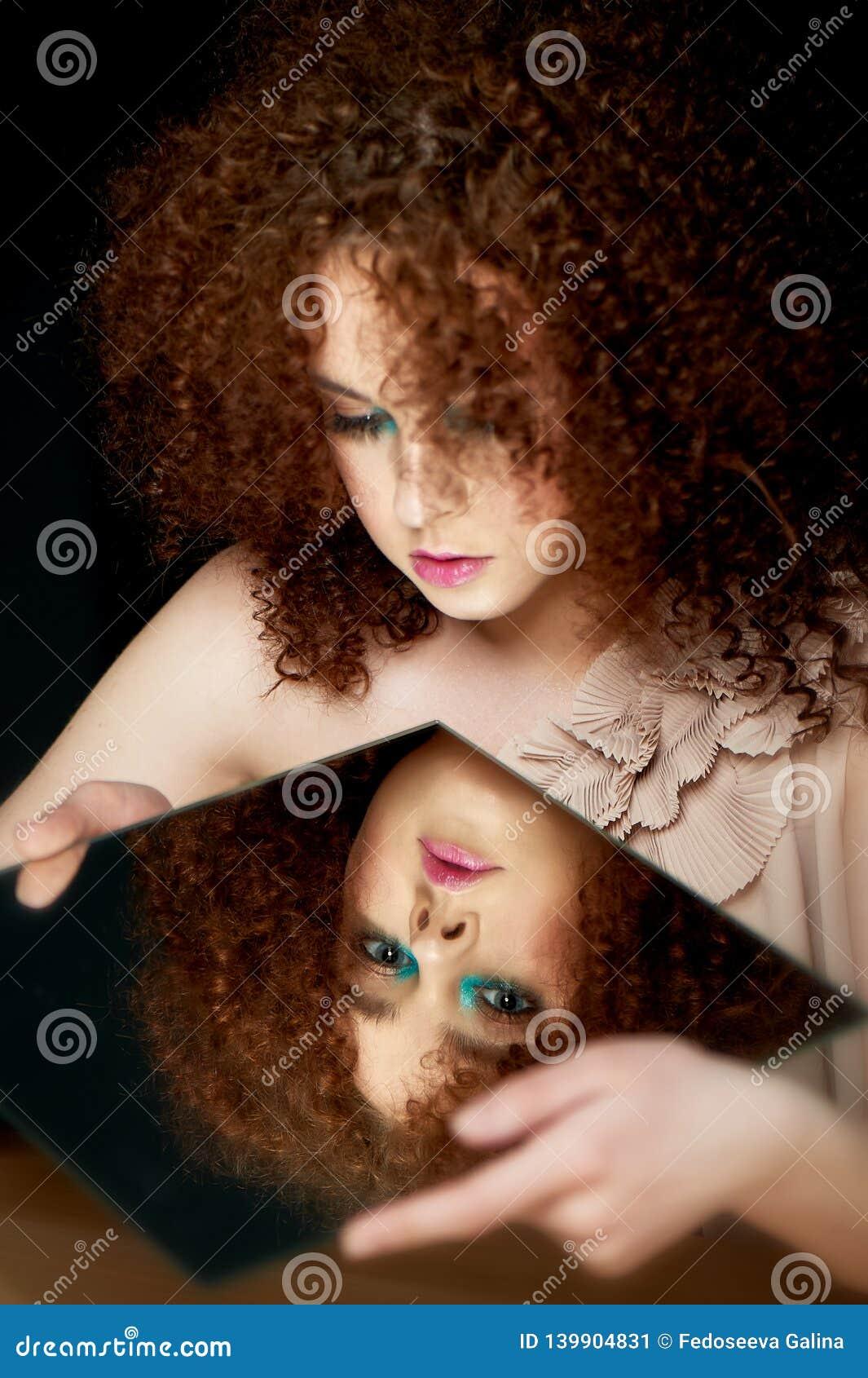 Девушка с сочными курчавыми красными волосами смотреть зеркало Тайна, предчувствие будущего его отражение внутренний взгляд