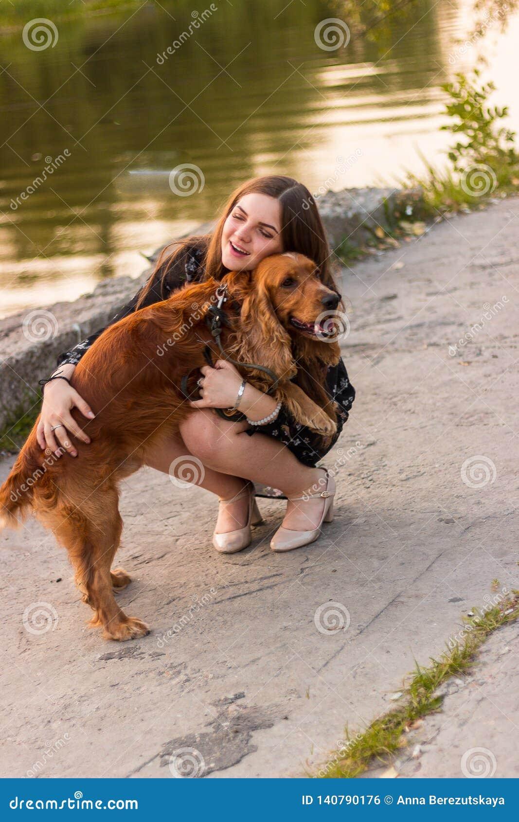 Девушка обнимая заключение крупного плана милой прелестной красной собаки любимца собаки дружелюбное наблюдает смешные животные