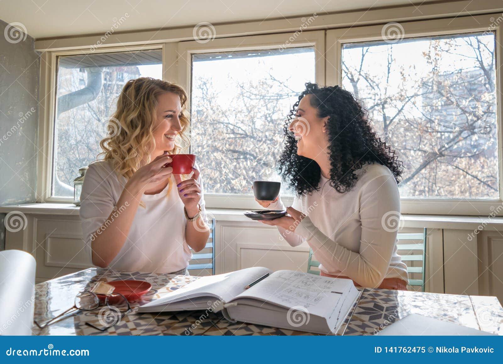 2 девушки выпивают кофе и смеются в кафе