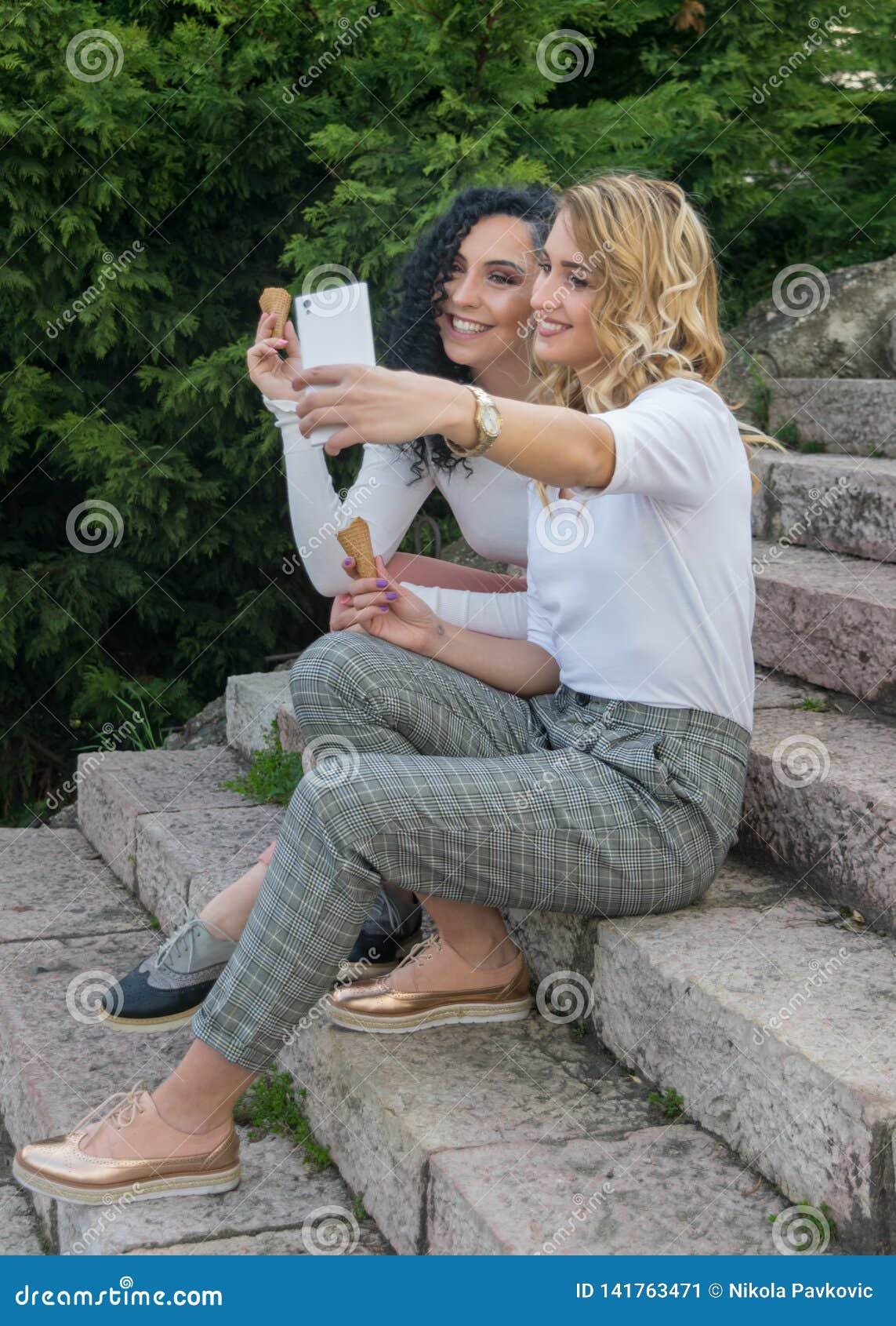 2 девушки принимают selfies и едят мороженое