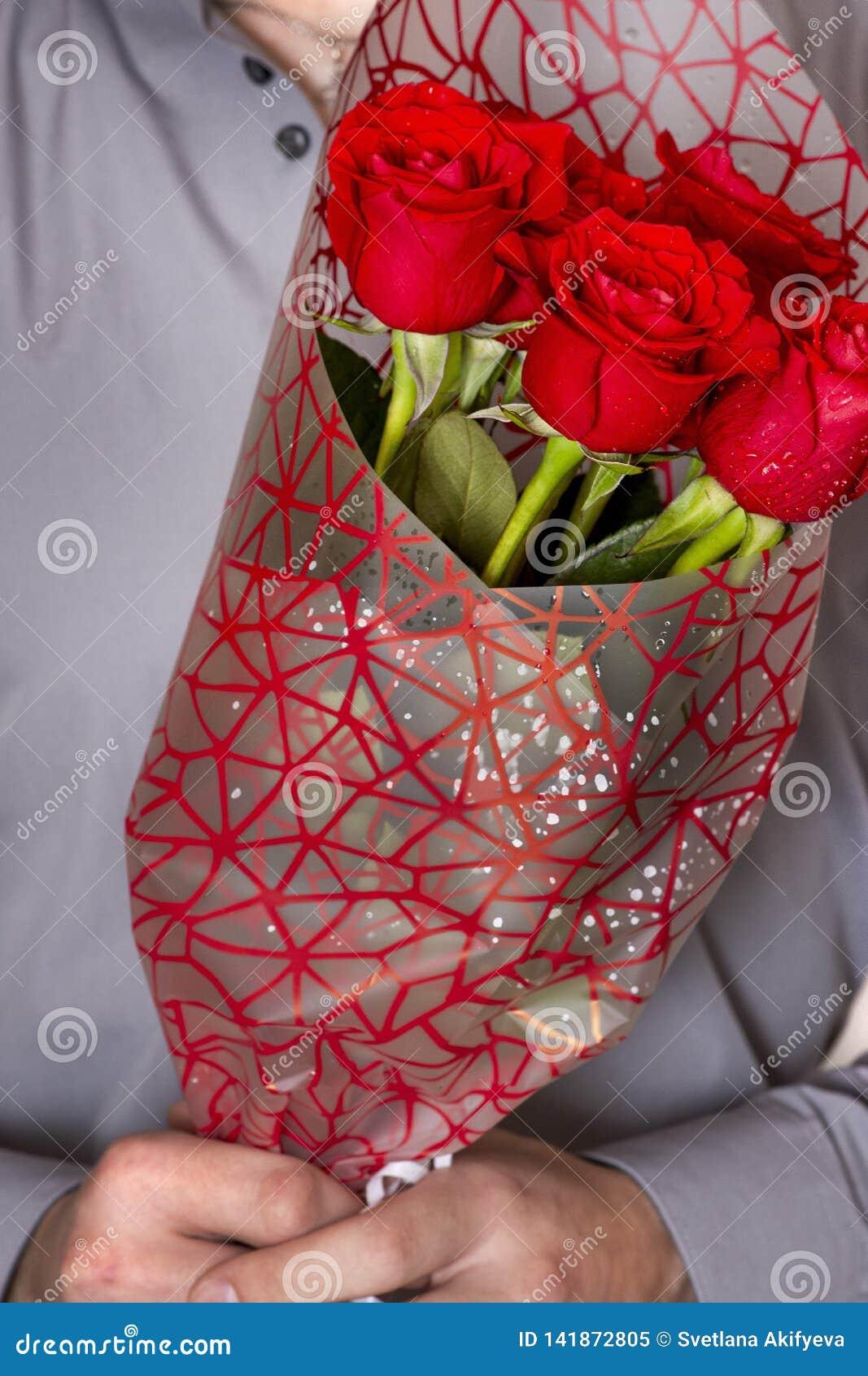 День или предложение валентинок Молодой счастливый красивый человек держа большой пук красных роз в его руке на серой предпосылке