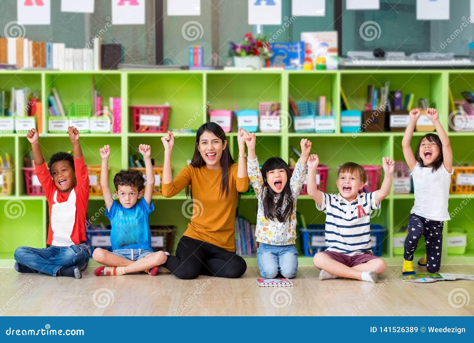 Дети счастливой азиатской учительницы и смешанной гонки в классе, концепции школы детского сада pre