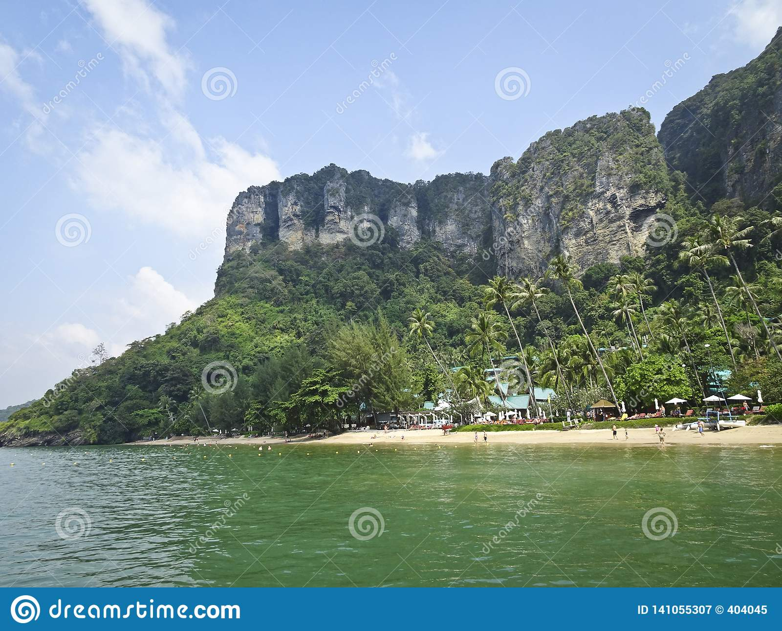 Деревня курорта на пляже под горой со скалистыми крутыми скалами, пальмами, желтым песком, лазурным морем