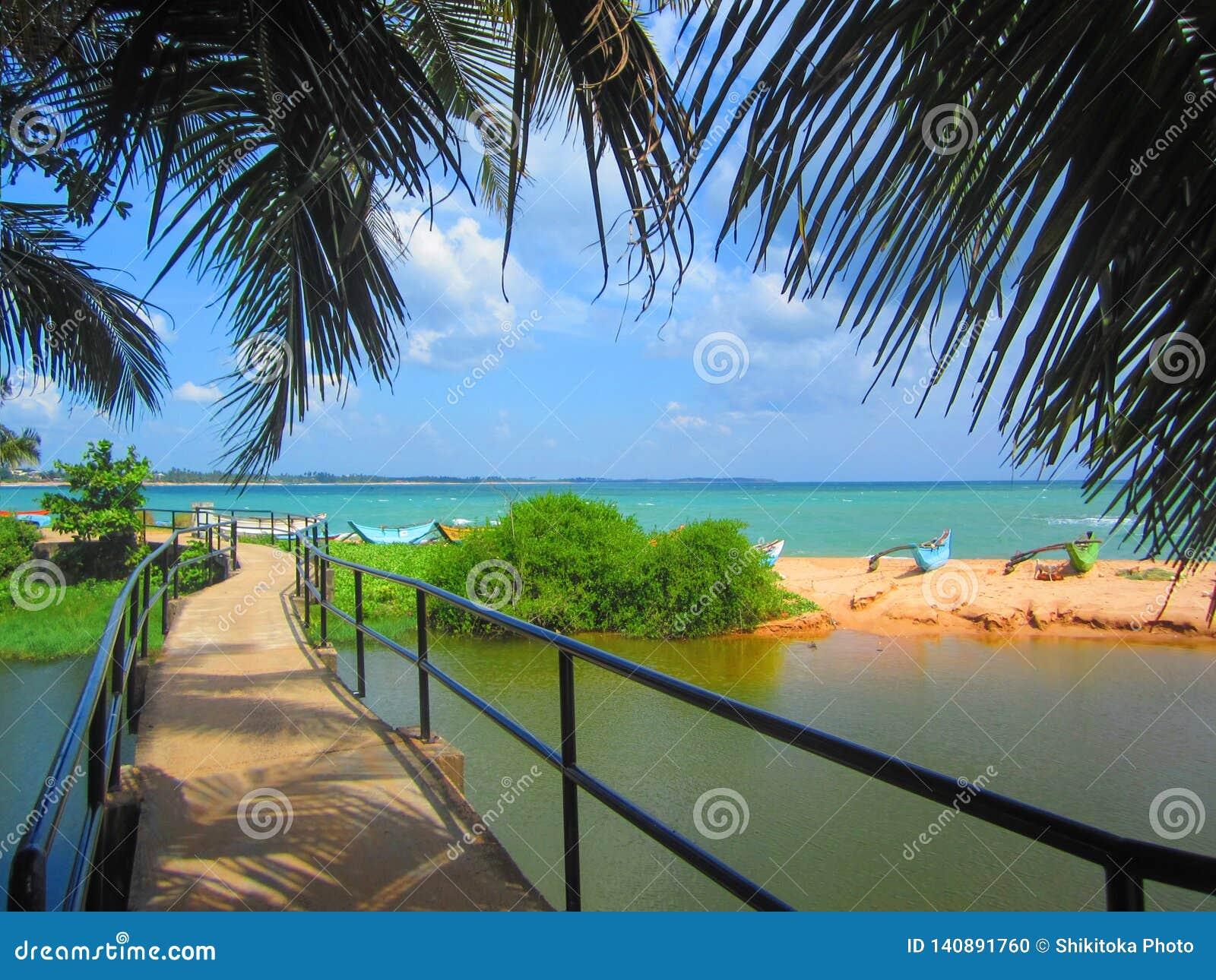 Деревянный footbridge над озером к пляжу моря с рыбацкими лодками