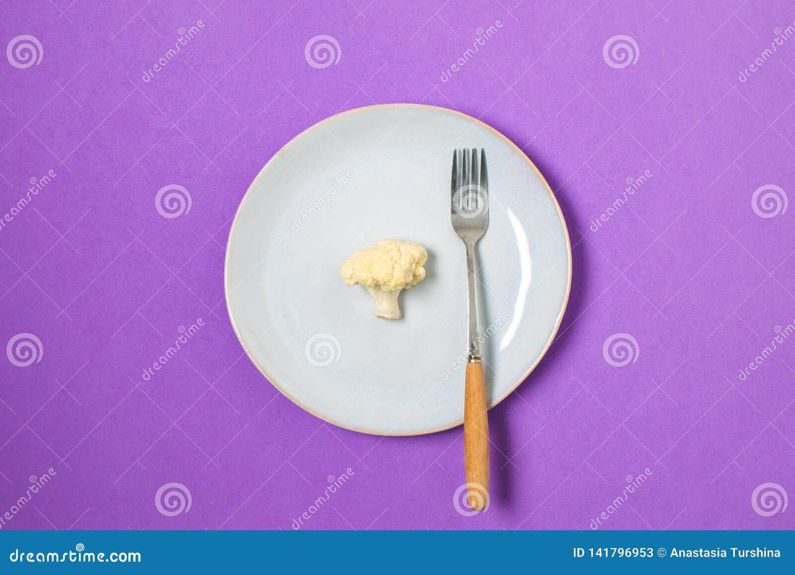 Диета, концепция потери веса минимальная, здоровая еда - цветная капуста на плите, космосе экземпляра, пурпурной предпосылке