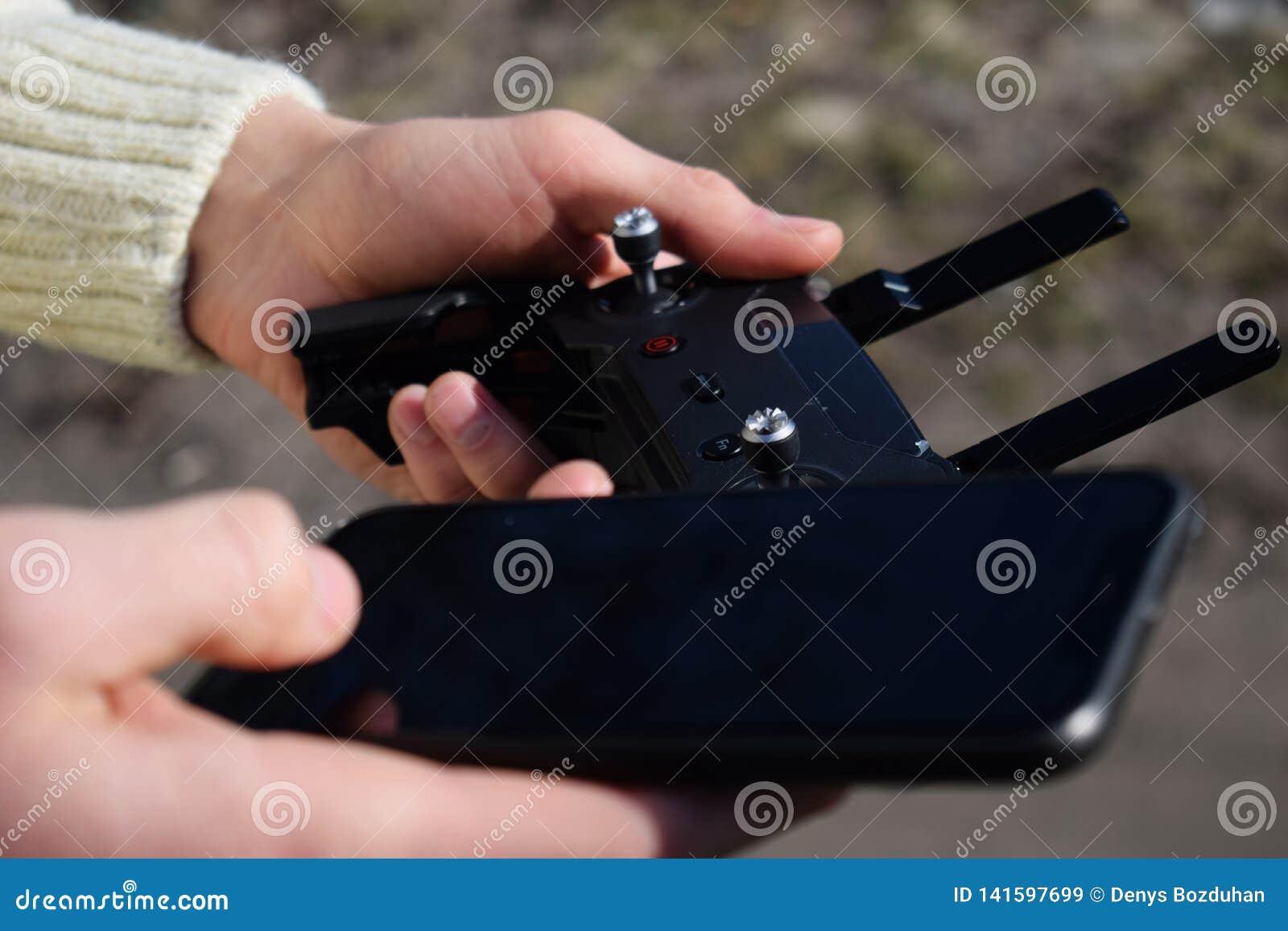 Дистанционное управление и смартфон в мужских руках Человек держа передатчик и пилотируя некоторые корабли Трутень, радио контрол