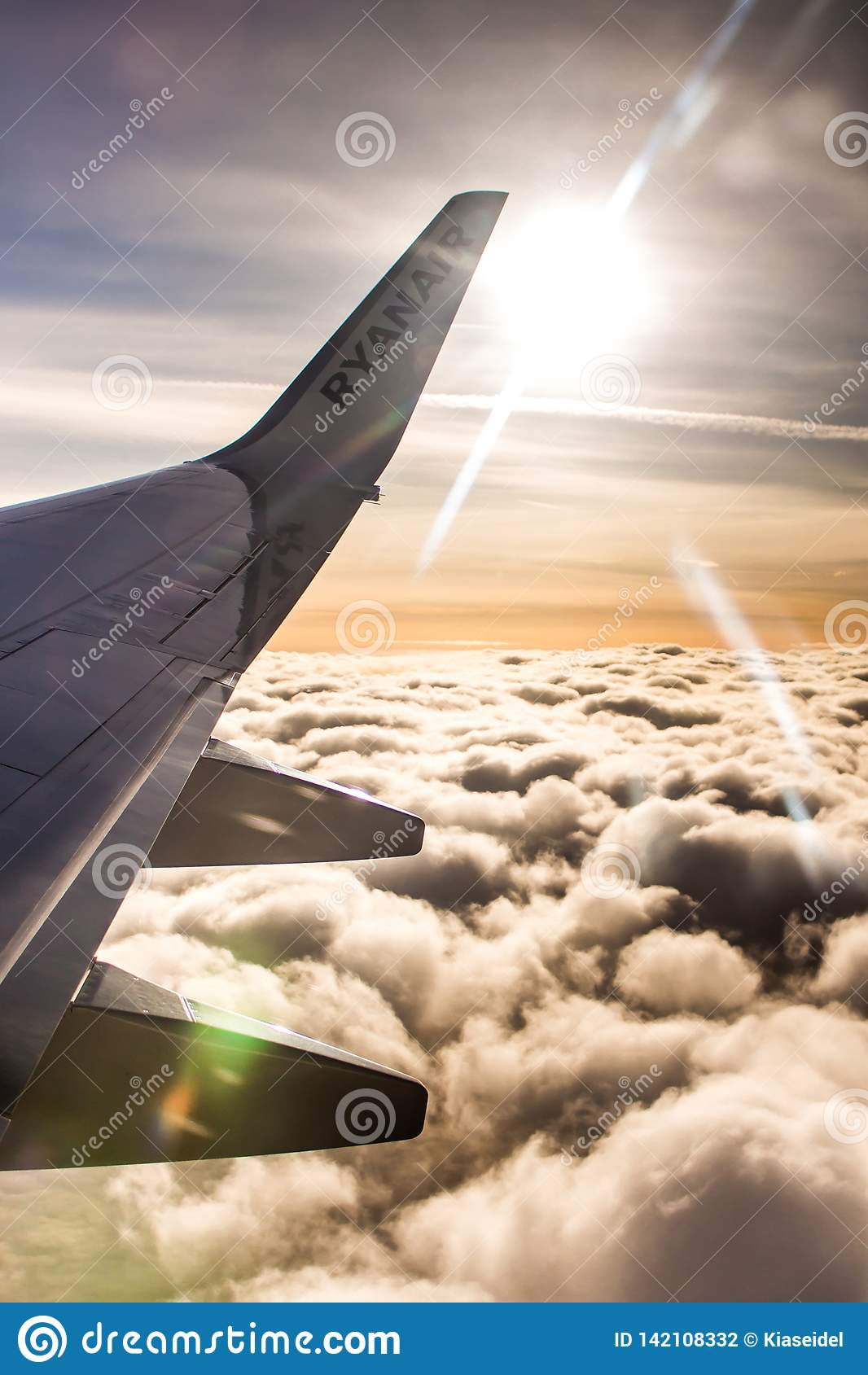 ДУБЛИН, ИРЛАНДИЯ - 23-ЬЕ АПРЕЛЯ 2017: Логотип Ryanair в крыле самолета с небом как предпосылка Ryanair имеет дешевые полеты