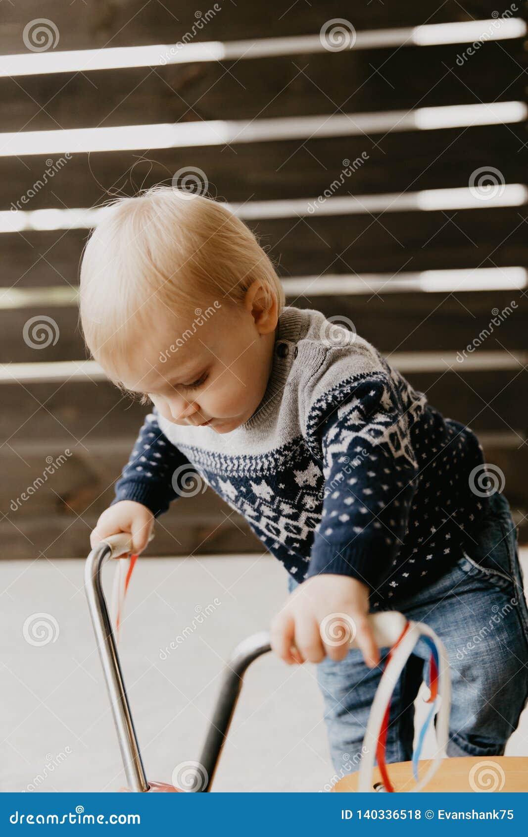 Драгоценный прелестный милый маленький белокурый ребенк мальчика малыша младенца играя снаружи на деревянной черни скутера велоси