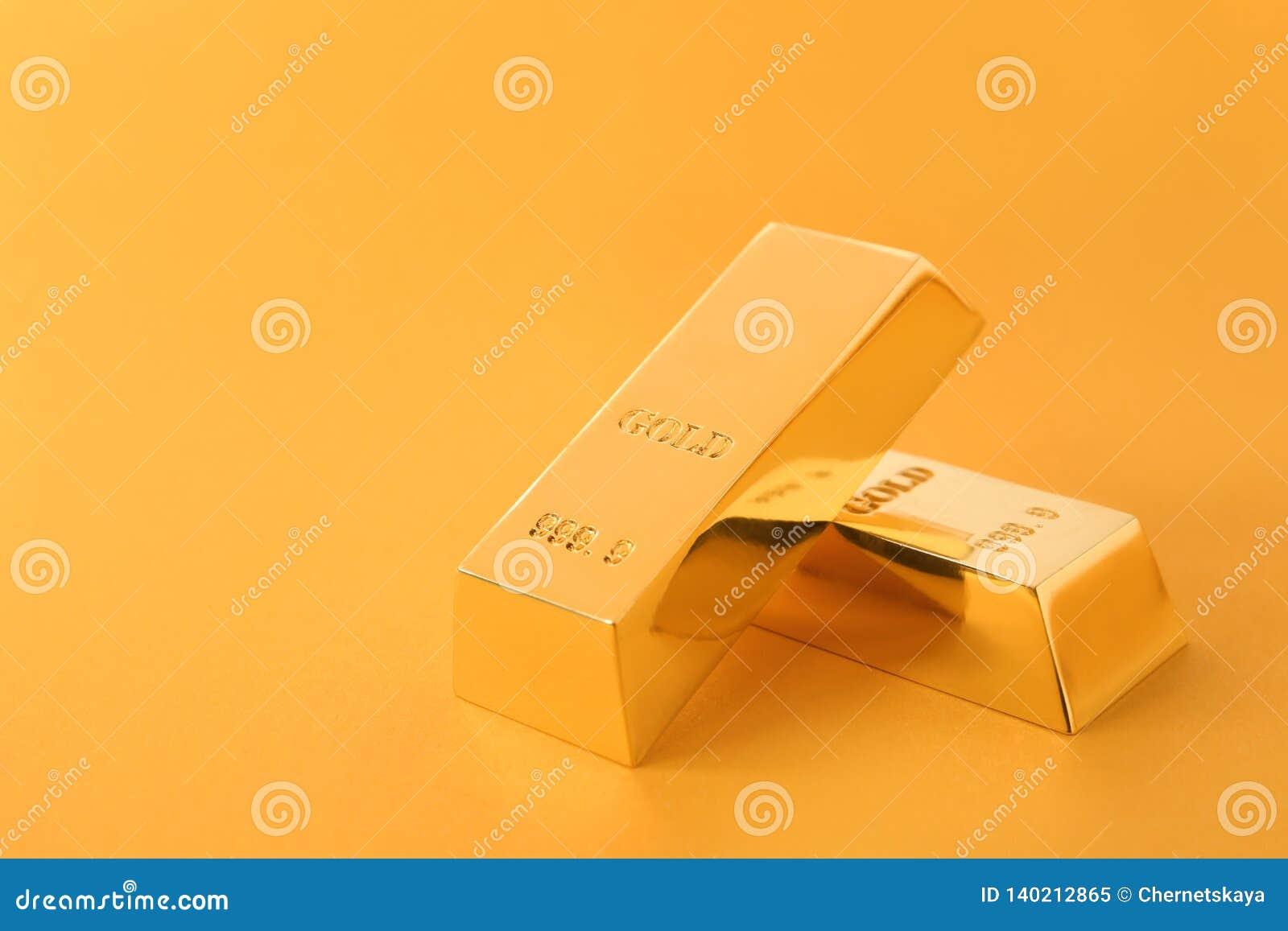 Драгоценное сияющее золото в слитках на предпосылке цвета