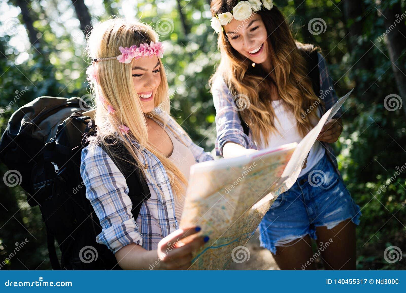 Друзья женщин Hiker с рюкзаком идя на путь в лесе лета