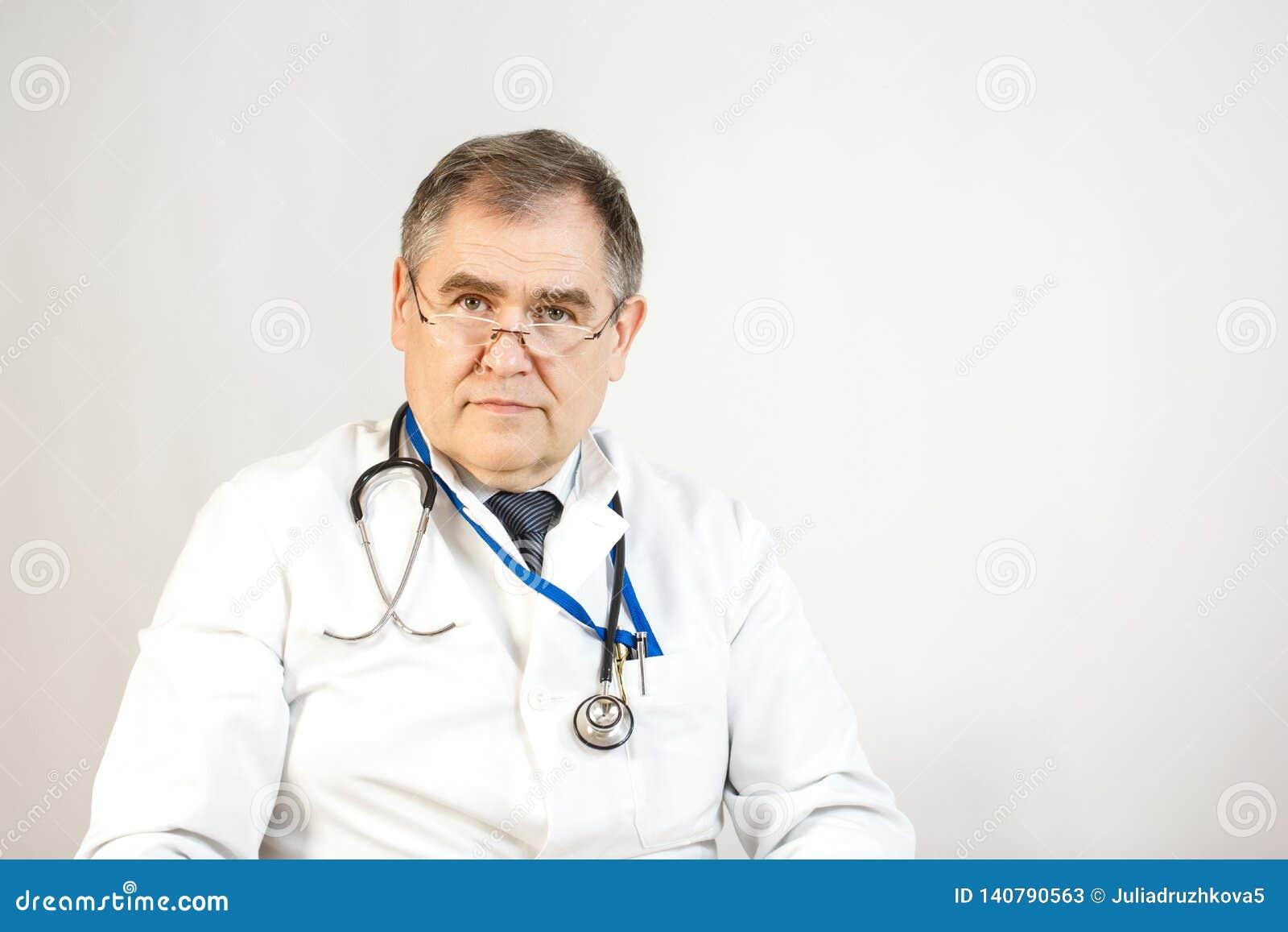 Доктор в белых пальто и связи смотрит вперед, whist имеет стетоскоп и значок на его шеи, и ручки в его