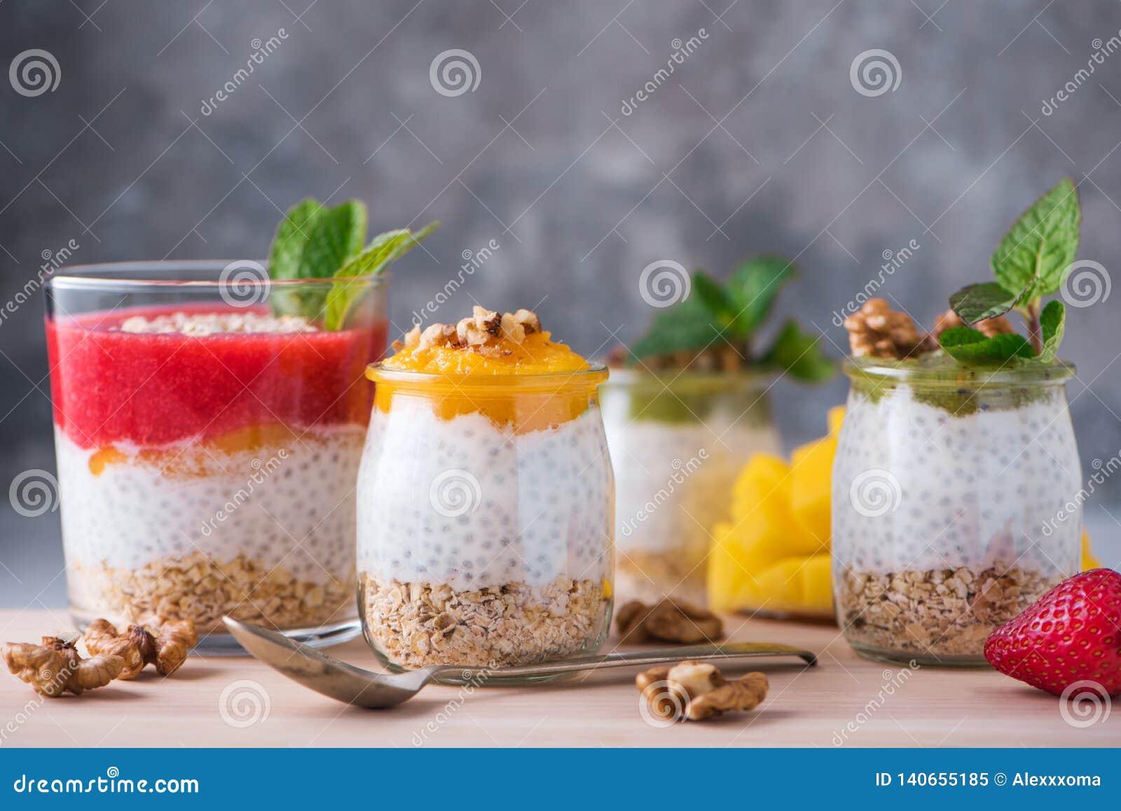 Домодельный пудинг семян Chia и молока миндалины с хлопьями и пюрем кивиа, клубники и манго с грецкими орехами и мятой в стекле