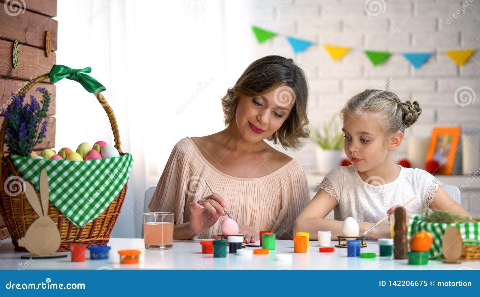 Дочь мамы уча как покрасить пасхальные яйца, семью подготавливая на праздник