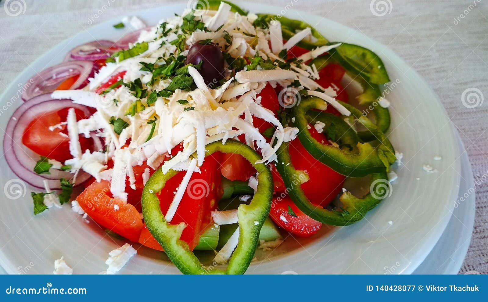 Салат в белой плите с луком, оливками и заскрежетанным сыром