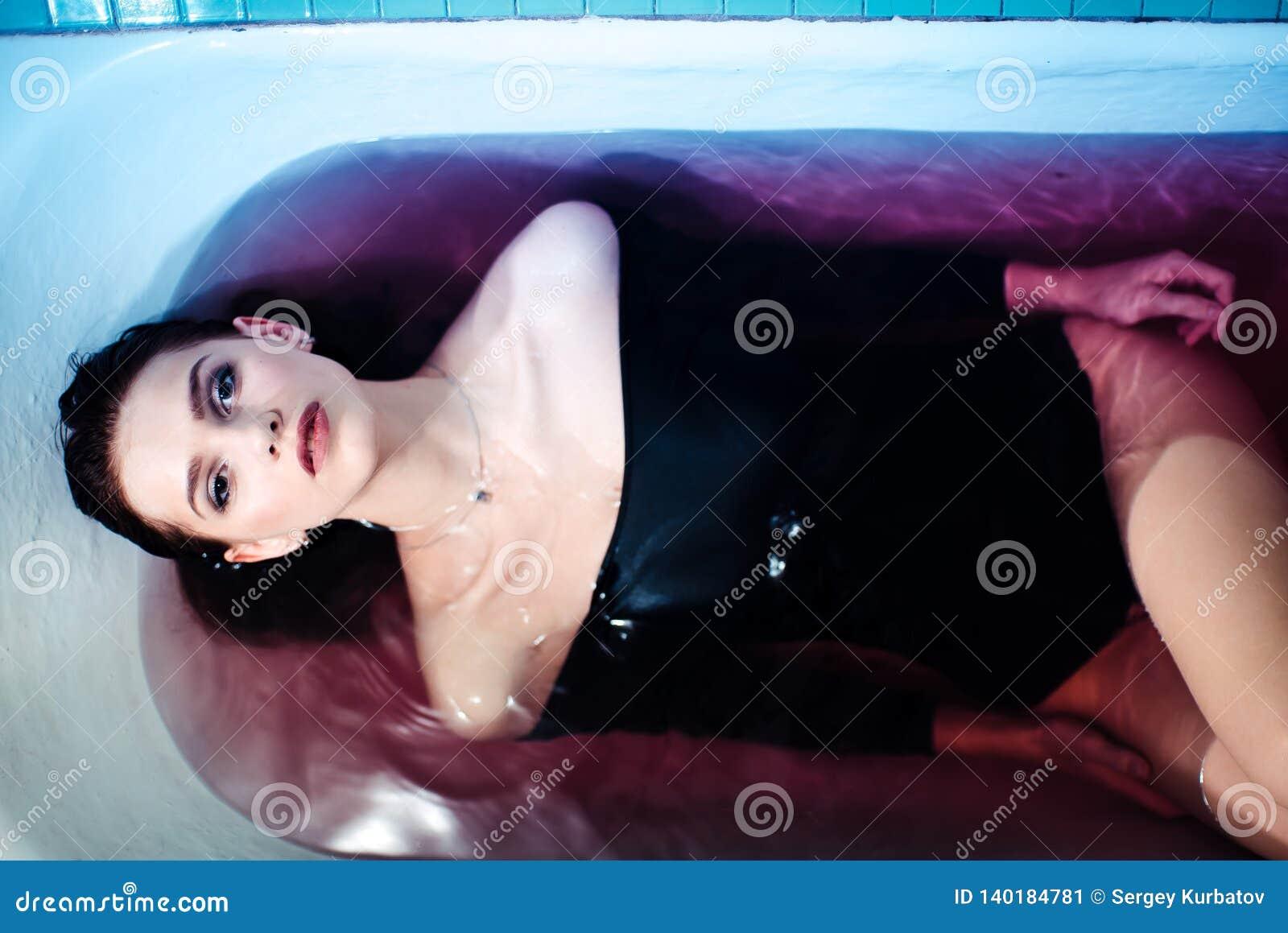 Сексуальная женщина в bodysuit в ванне Яркий свет и покрашенная вода чуть-чуть плечи