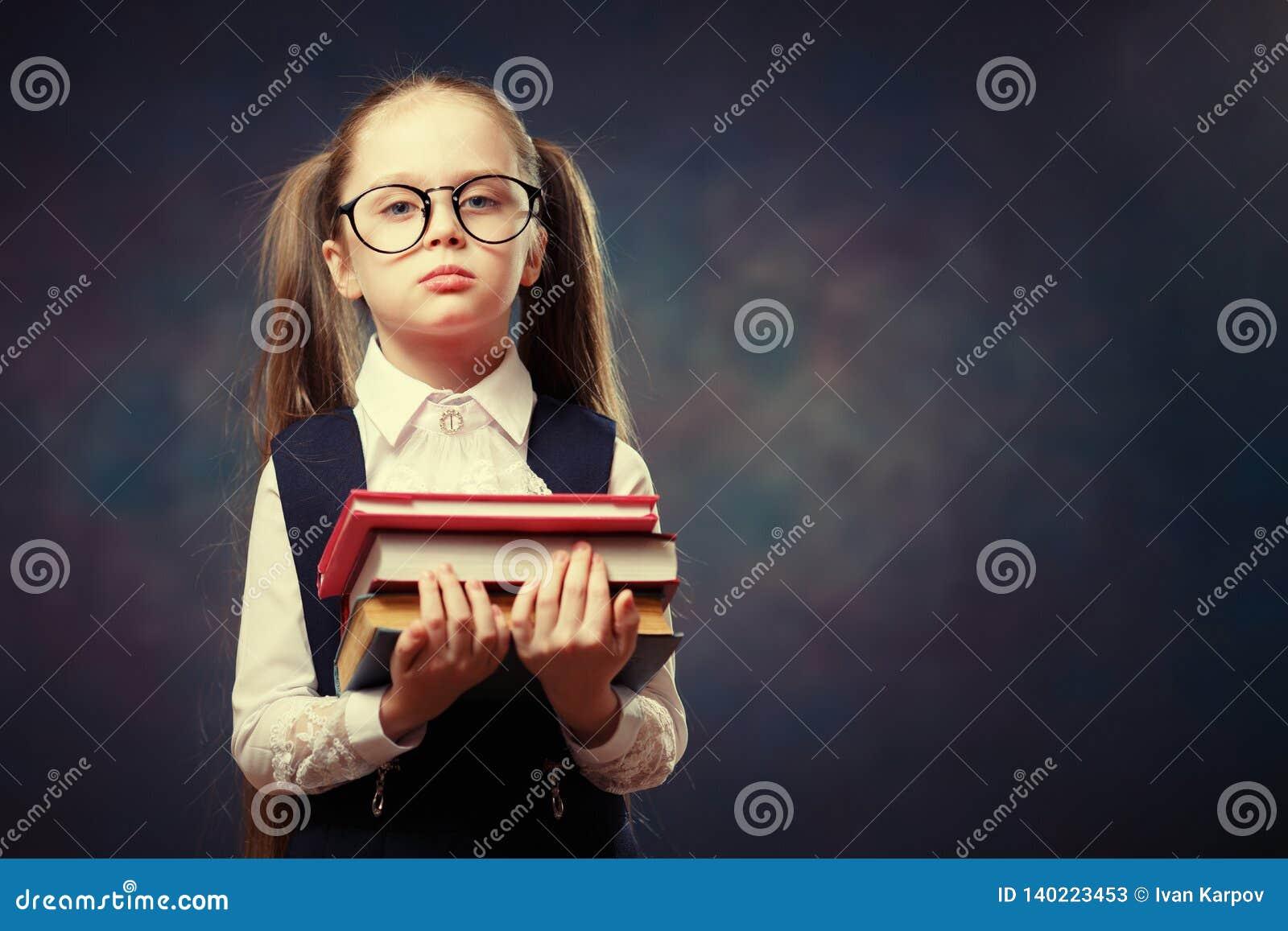 Серьезные стекла носки школьницы держат кучу книги Тон цвета