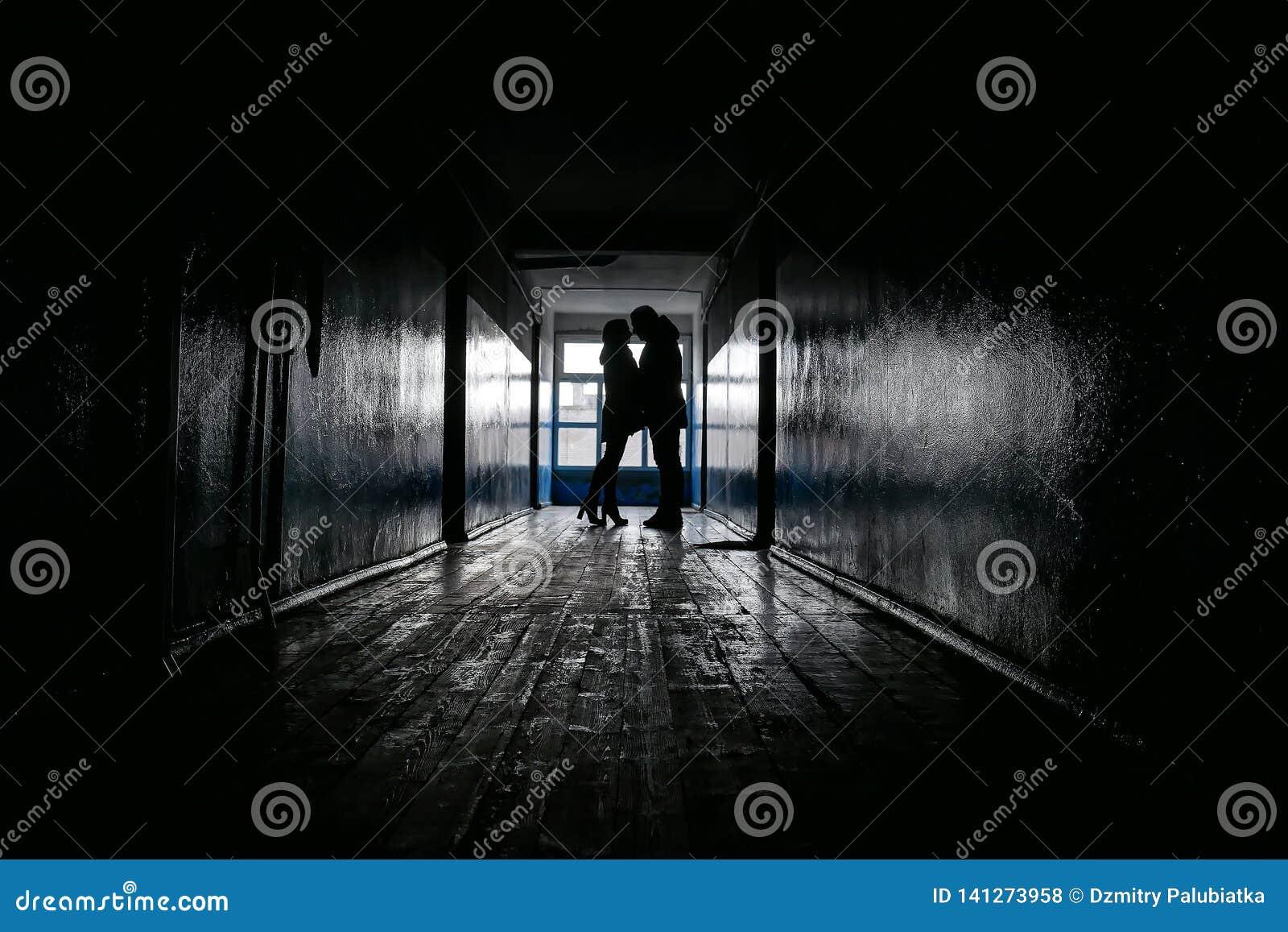 Силуэты 2 любовников в темном коридоре