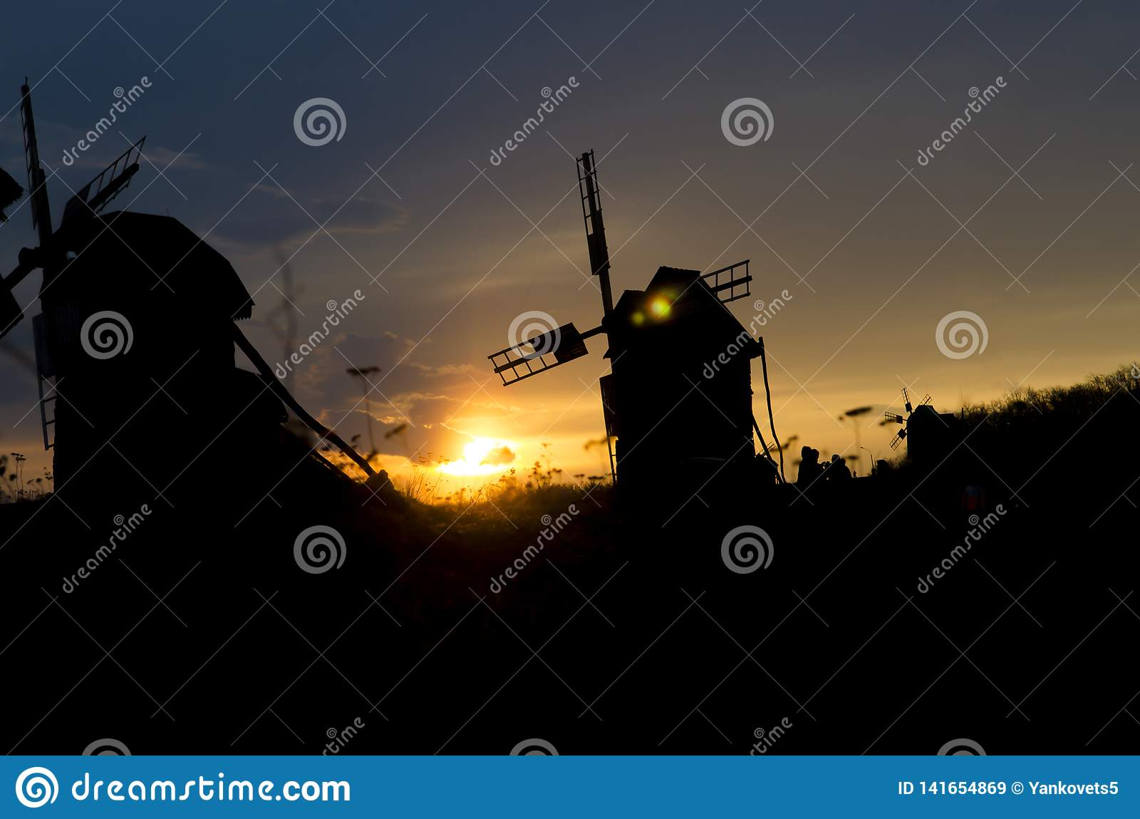 Силуэты старых ветрянок на предпосылке яркого захода солнца голубого неба