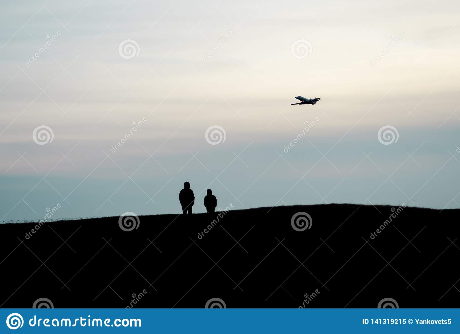 Силуэты стойки 2 людей на высоком холме и наблюдать максимум летания самолета в небе