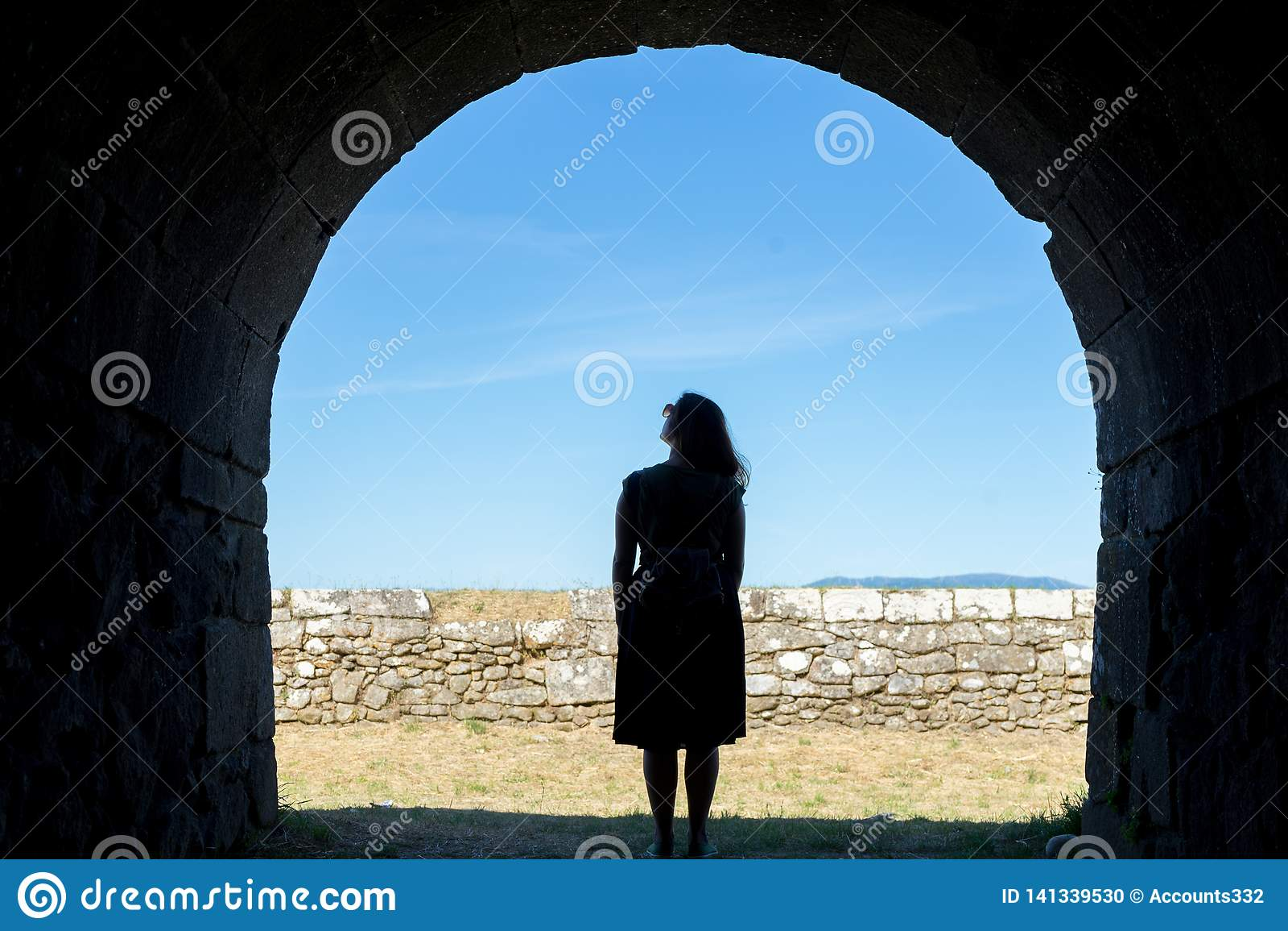 Силуэт женщины на старом каменном тоннеле
