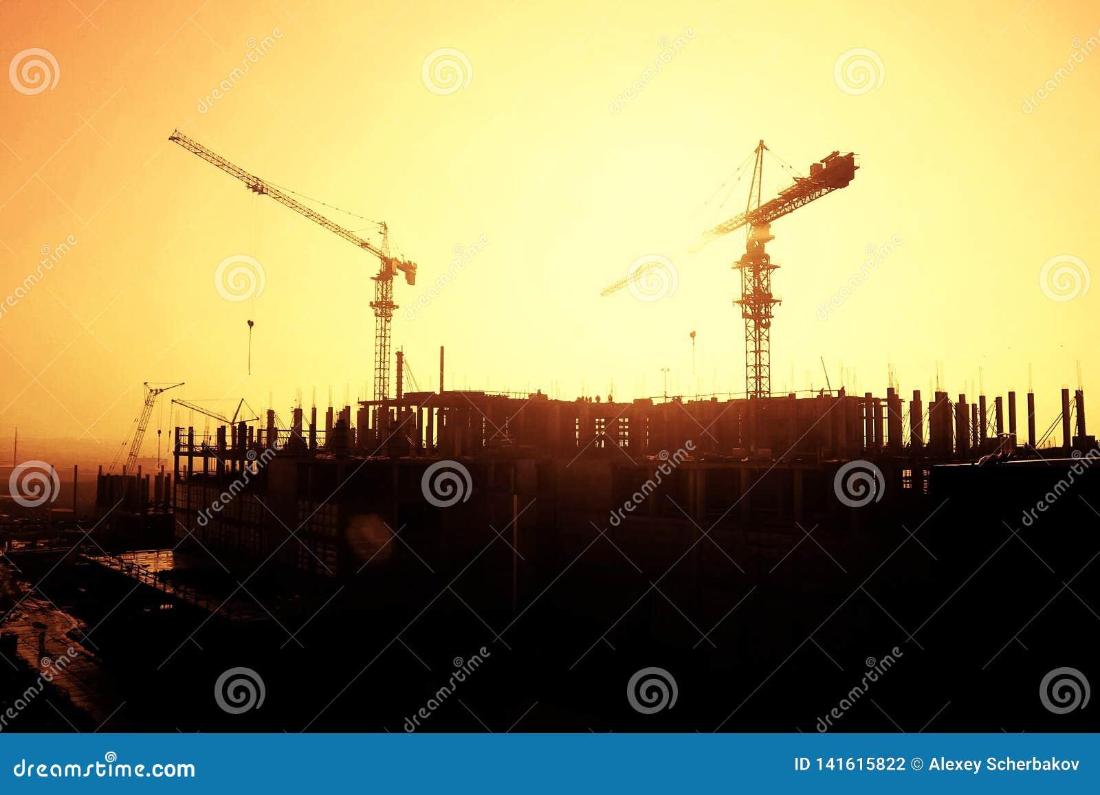 Силуэт крана и рамки здания под конструкцией на предпосылке захода солнца
