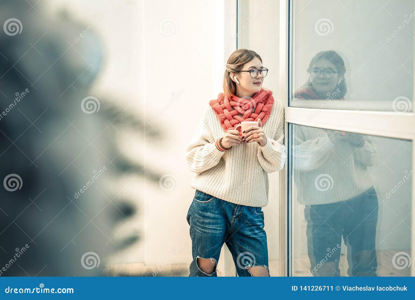 Симпатичная стильная дама оставаясь с чашкой чаю и нося связанным обмундированием