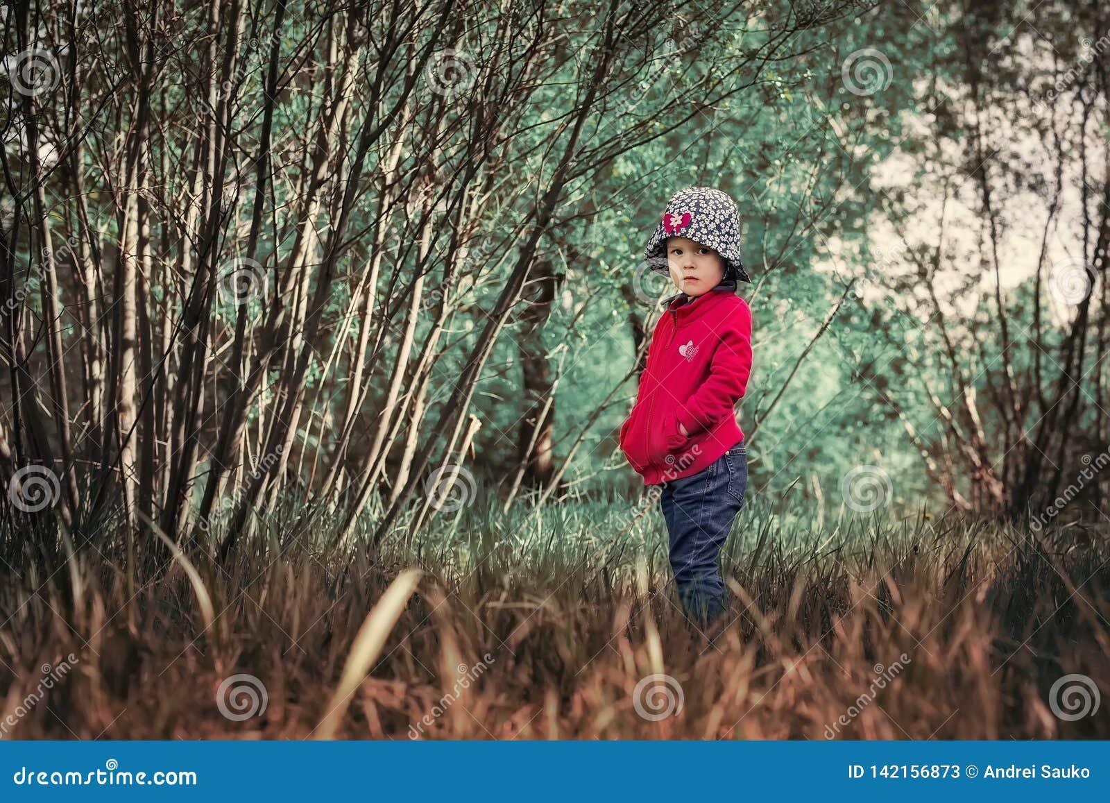 Сиротливый серьезный ребенок в волшебном лесе