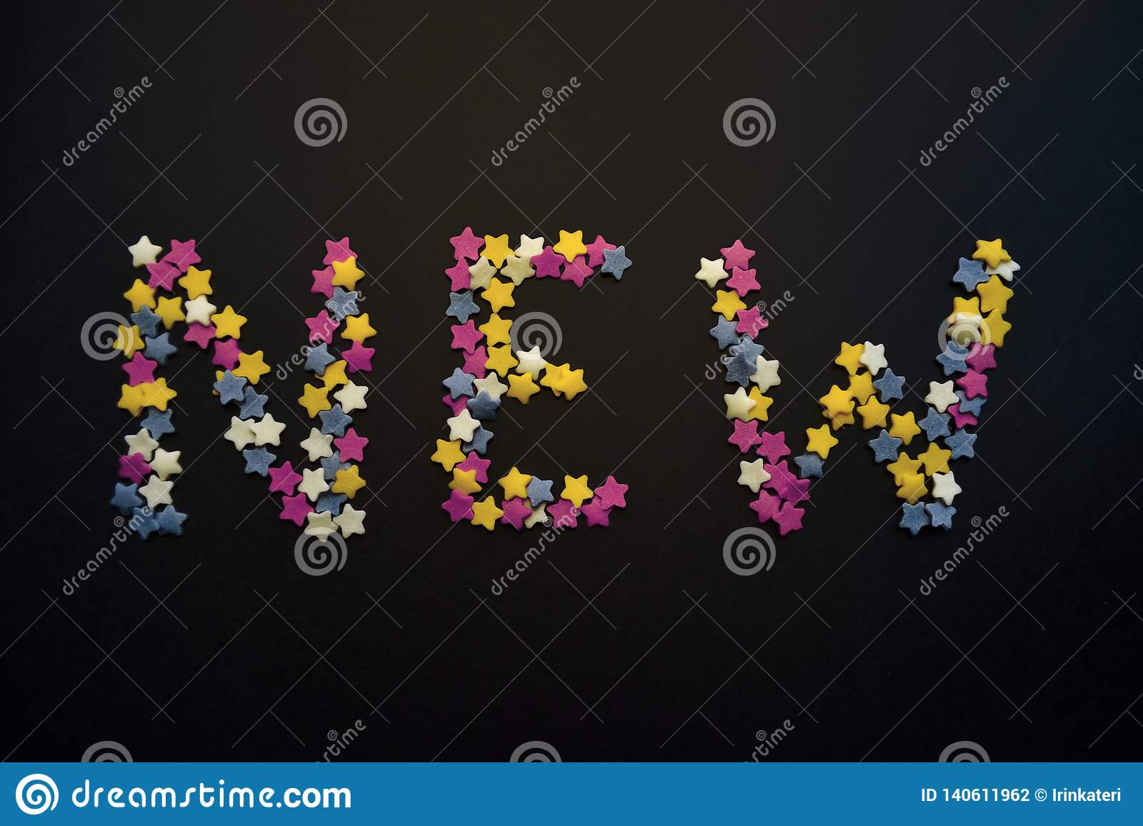 Слово новое написано в толстом типе звезд печенья сахара на черной предпосылке, для, реклама, коммерция, продажи